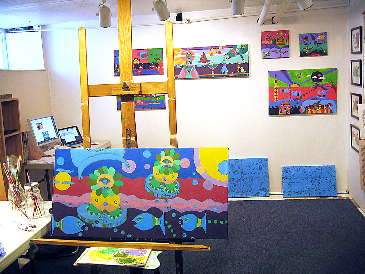 The working studio with finished pieces on the wall, some framed drawings to the right and unfinished canvases on the floor and easel.