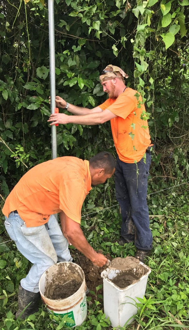 Barry and Edwin cementing in a fence pole