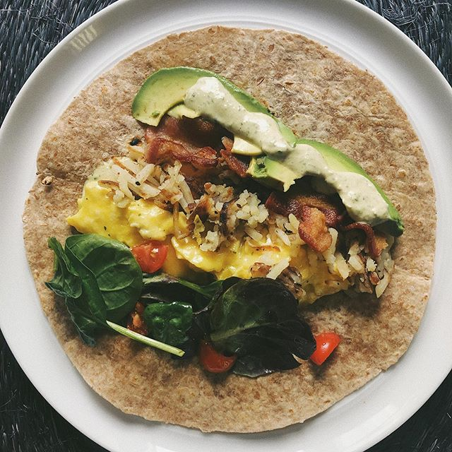 a healthy-ish breakfast burrito 🌞 I made this yesterday & I'm making it again today! sprouted @alvaradostreetbakery tortillas, scrambled eggs w/ sharp cheddar cheese, shredded hash browns, @applegate bacon, spinach & tomato tossed in mediterranean olive oil and sliced avocado with @mothersmarkets cilantro jalapeño dressing. Hope everyone enjoys their day & gets out and does something that makes them happy. I love Sundays 🌞#eatprettywitherika #pairedwithsunshine #breakfastburrito