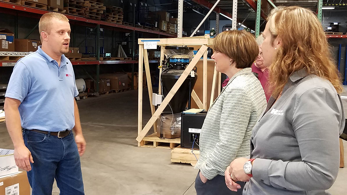 Production Supervisor Jordan Honnette greets Sen. Klobuchar as the tour reaches Kahler Automation's production area.