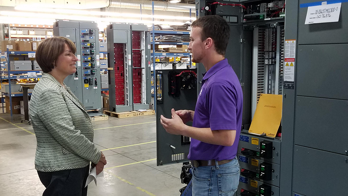 Electrical Designer Cole Lightfoot describes the function of Kahler Automation's motor control centers to Sen. Klobuchar.