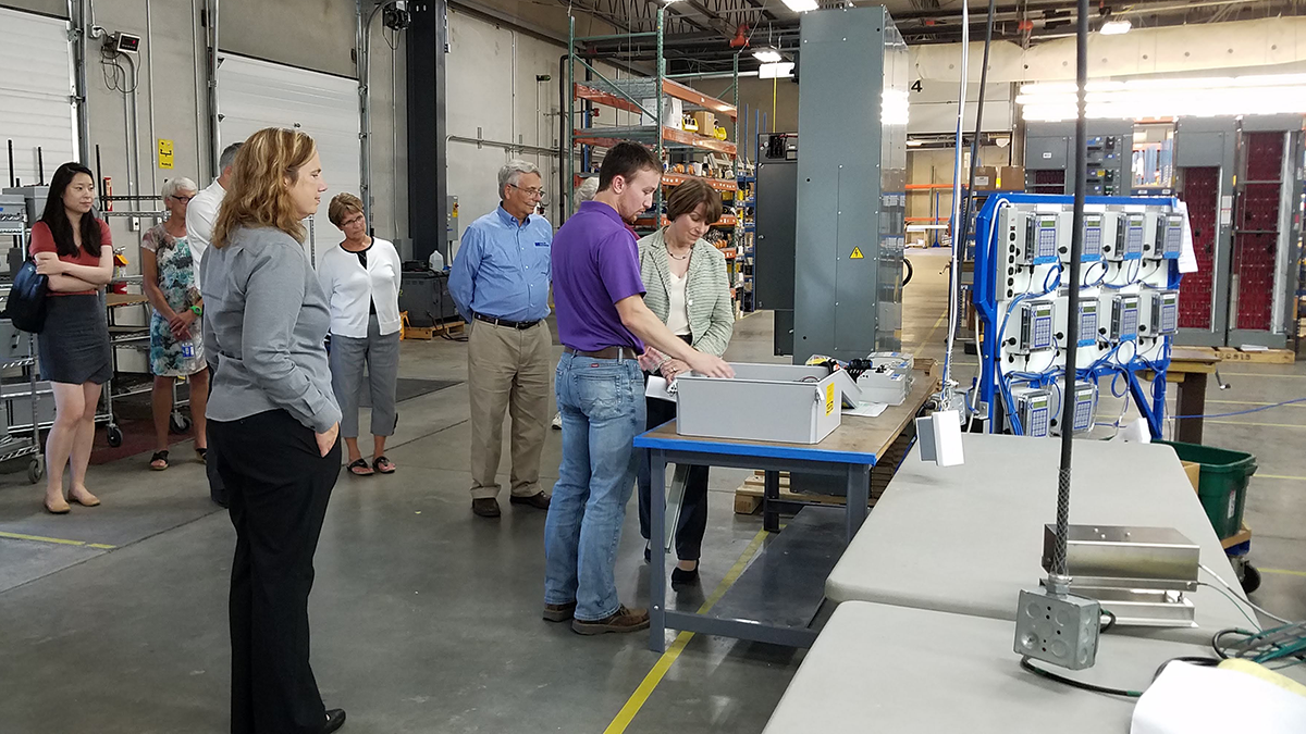 Cole Lightfoot explains to Sen. Klobuchar the inner workings of Kahler Automation control systems, as the rest of the tour group looks on.