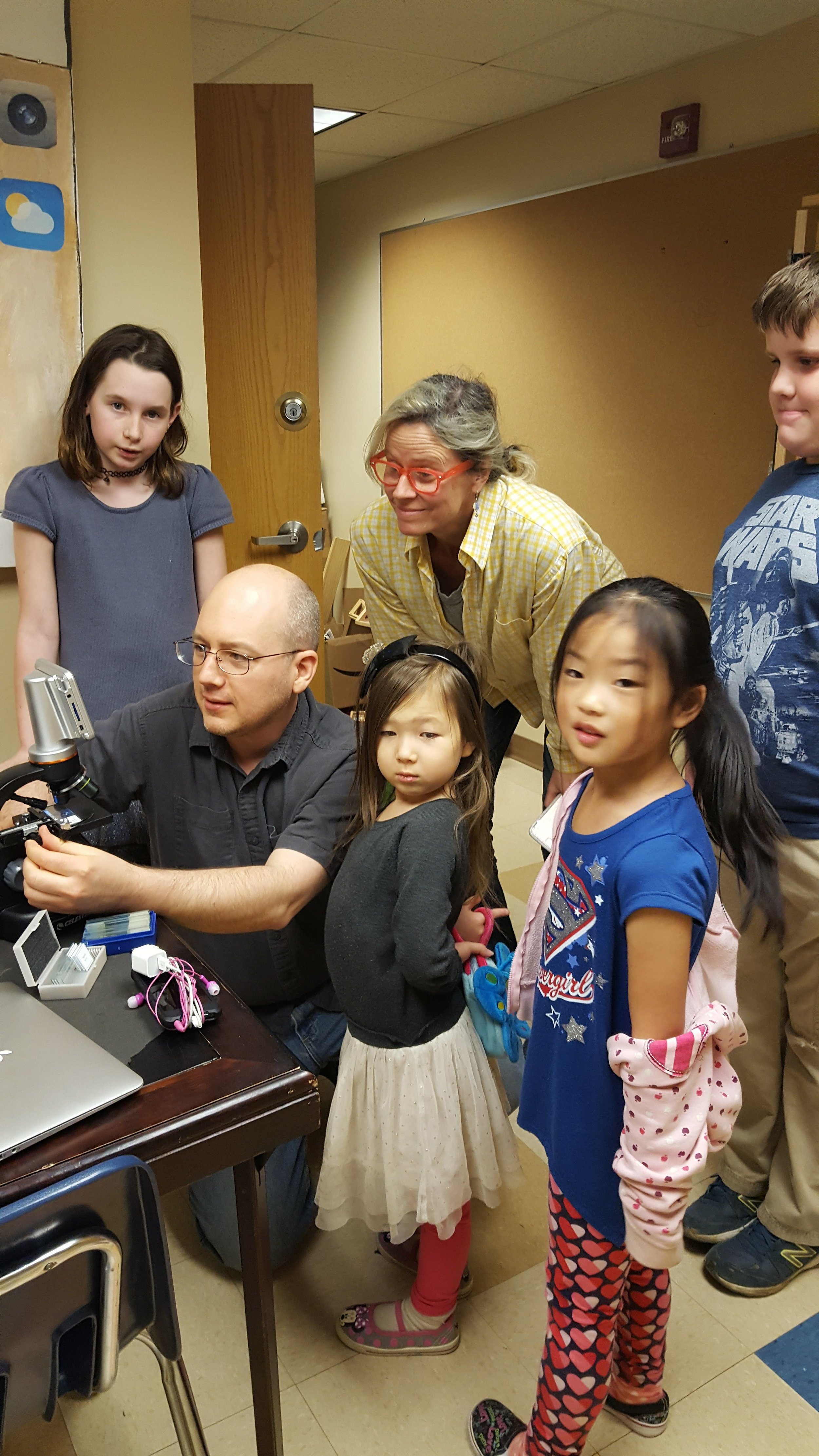 Staff figure out how to use a new microscope as students look on at A&I in Baltimore. Other staff jobs: giving out band-aids, emptying trash cans, answering questions, paperwork, advocating for the philosophy of the school.