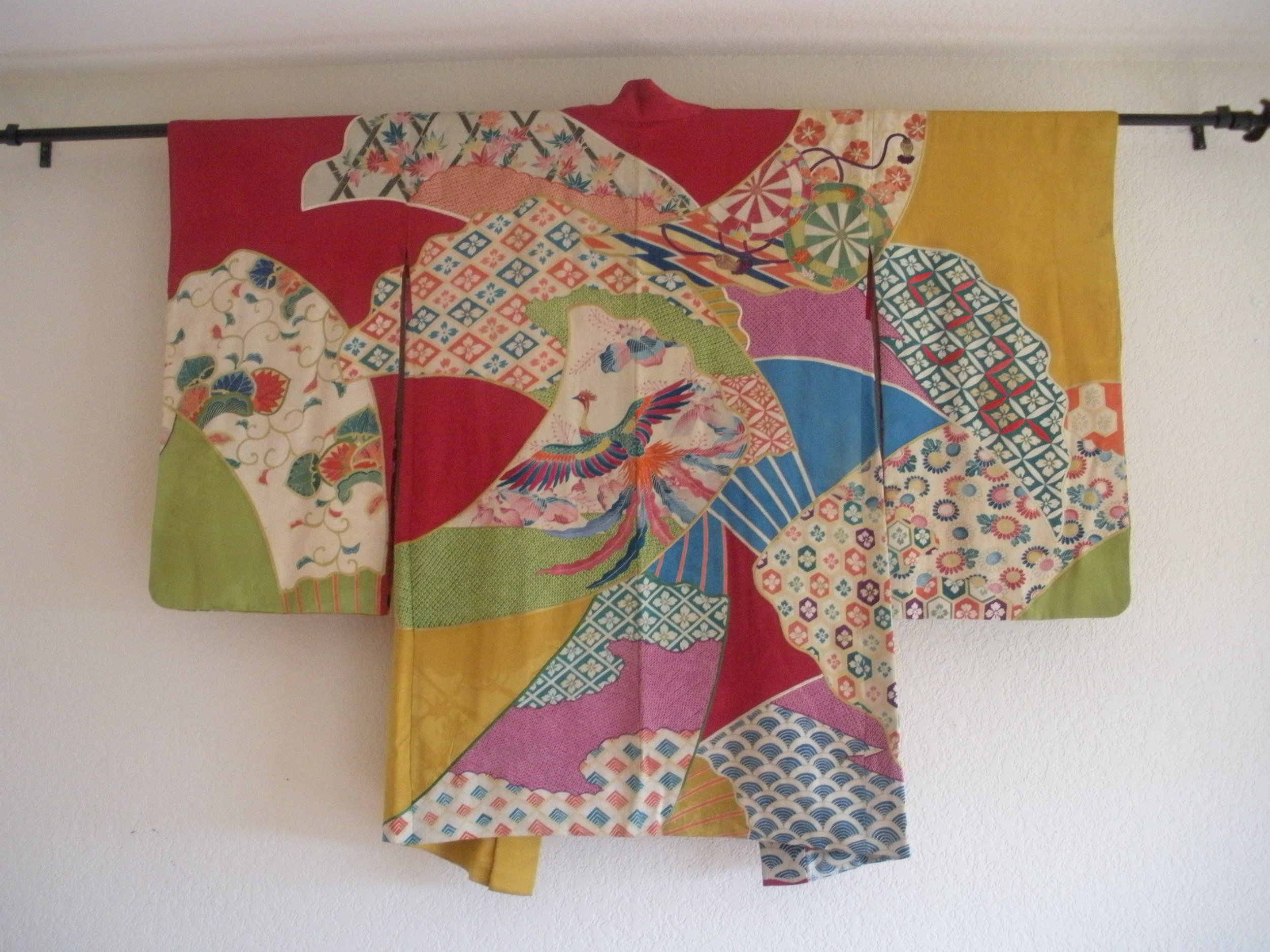 """This is a very cool haori we collected. It has good length, like a Taisho Piece, except the condition is just too good. As the Japanese dealers would say: """"sen-zen, sen-go."""" Basically, before or after the war. Sorry if that's vague. There's a brilliant hand embroidered phoenix in colors that invoke for me a Hokusai crane I saw at a museum once. The self is unique: I've handled literally tens of thousands of haoris, but I've never seen one like this. It's oatched together of various kimono silks, mostly jacquards, with a ton of artwork including shibori and yuzen. The textiles are joined seemlessly, with embroidery all over the so it all looks like one textile. Not for sale, sorry."""
