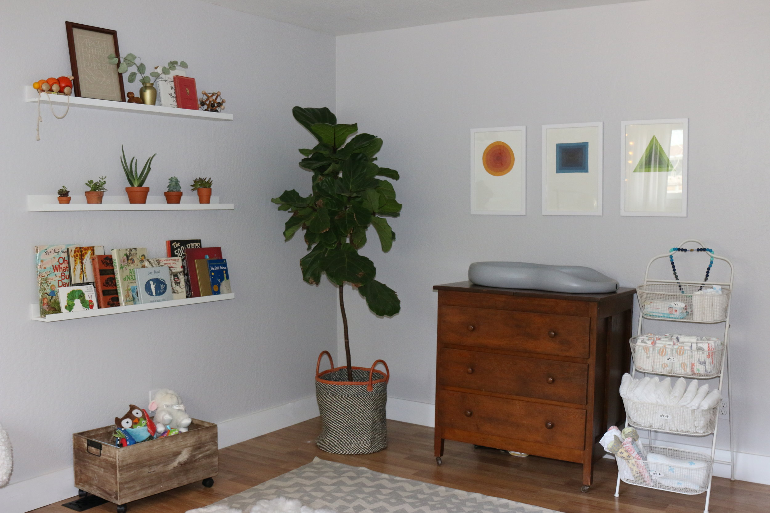 (IKEA shelves, Fiddle Leaf Fig from Home Depot, Basket from @safari_heidi, art from www.jaybryantjones.com who happens to be Daddy, organizer from Home Goods, rug from Urban Outfitters, dresser is a family piece, changing pad is called a Keekaroo Peanut, wood crate on wheels from Home Goods.)