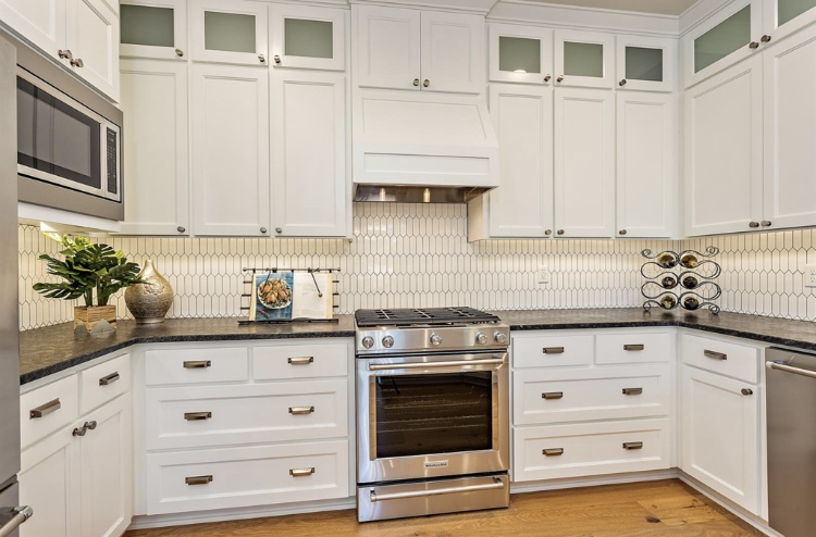 The brushed nickel cabinet and drawer pulls create a traditional and yet modern feel. The long, flat hex backsplash adds character and visual interest and yet doesn't compete with the rest of the kitchen details.