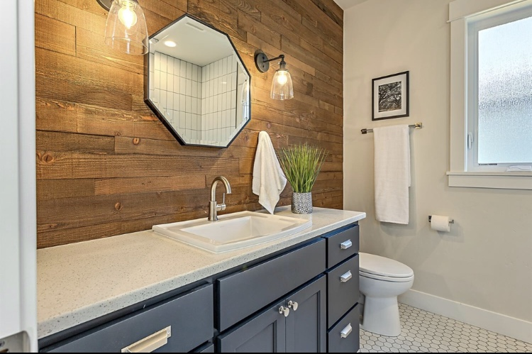 Guest Bath. The cabinets are painted in BM Wrought Iron. The white hex floors compliment the cute, hex mirror. The wood wall was created from the original Farmhouse that sat on this property.