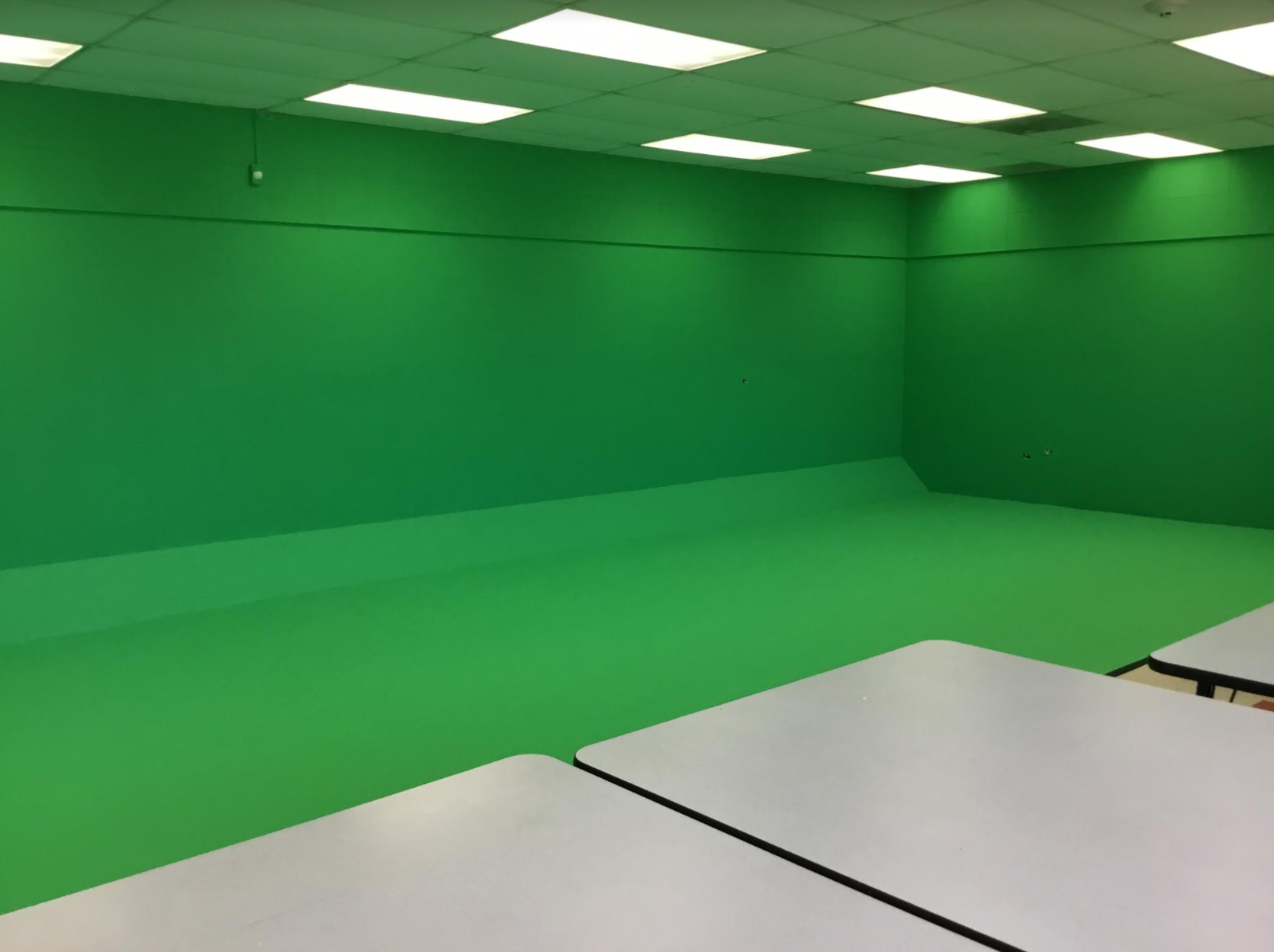 """Student Technology Leaders (STLs) at Ralph Bunche built a greenscreen """"Green Room"""" for teachers and students to take videos in. The """"Green Room"""" will allow students to do special effects and create high quality videos for their school."""