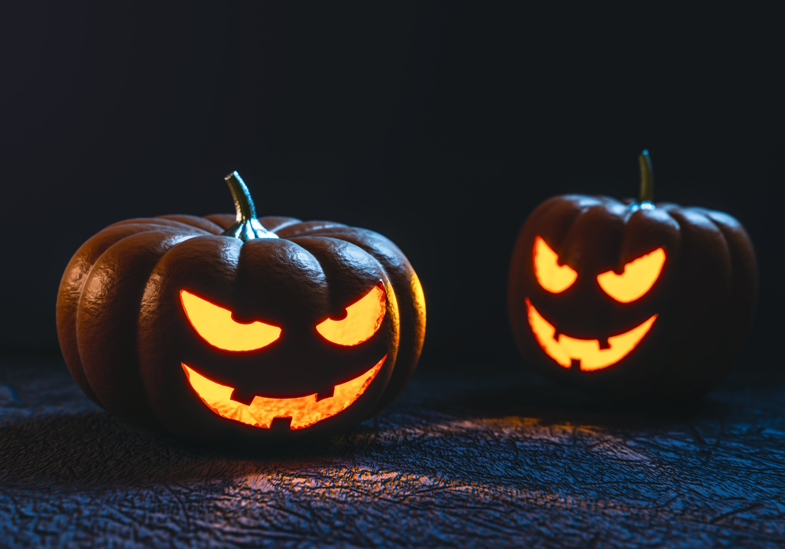 Two carved pumpkins with mischievous faces.