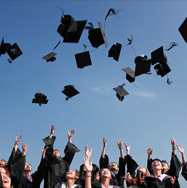 Students in graduation gowns throwing their caps into the air. Photo by Pixabay.com. Modified 5/9/2019