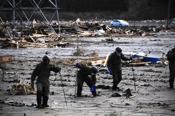 Rescue volunteers scour the mud in Fukushima for the deceased.