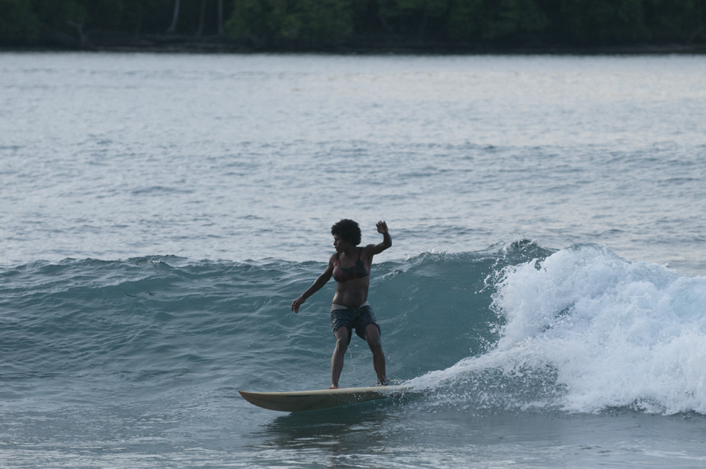 A new mum finishes breast feeding and heads out for a quick wave before dusk on the village's newly donated surfboard.