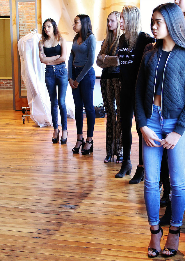 Models lined up for role call and run throughs with their designers and the KCFW Committee.