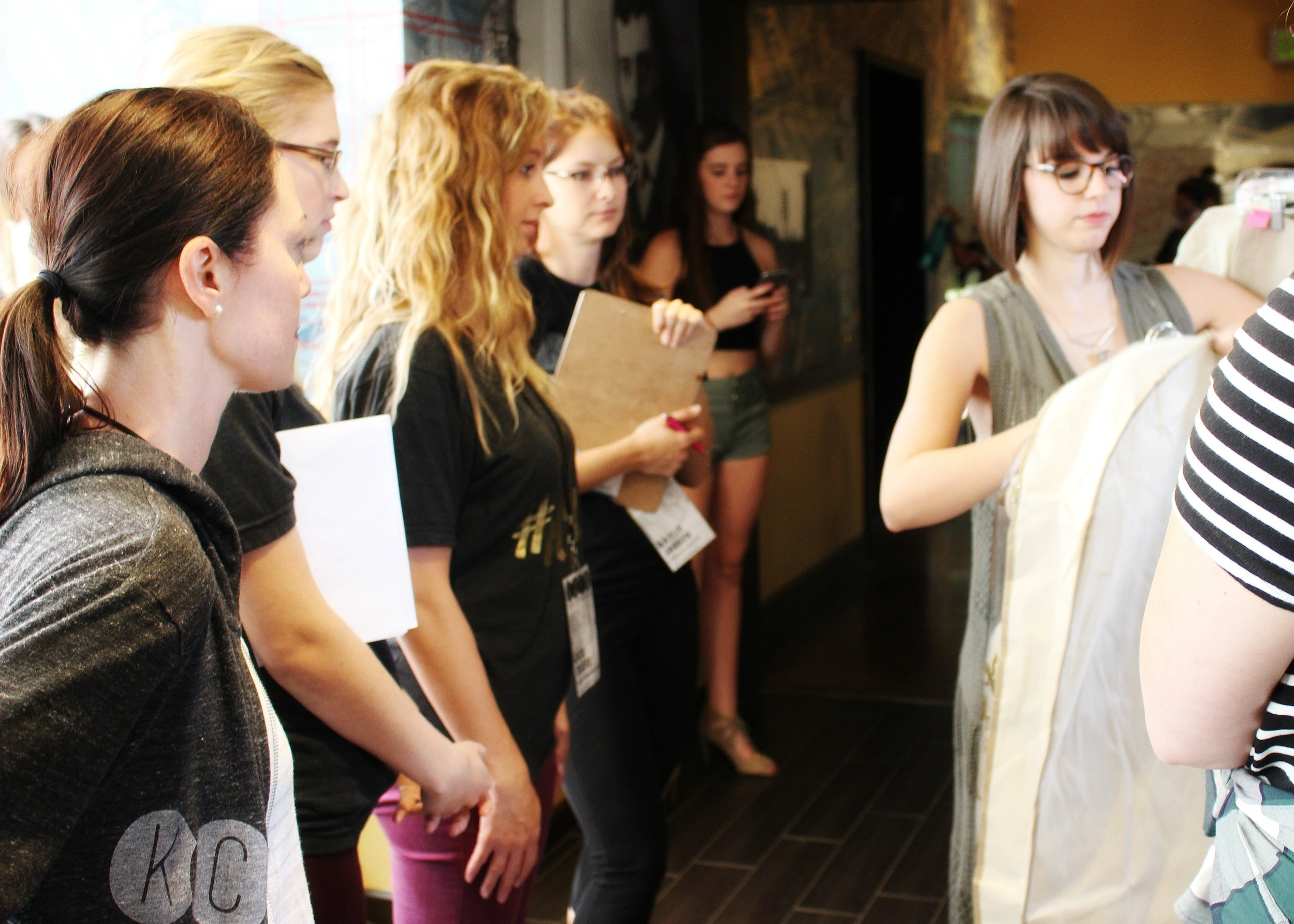 Designer Sara Kahrs shows her collection to the KCFW committee during rack checks.