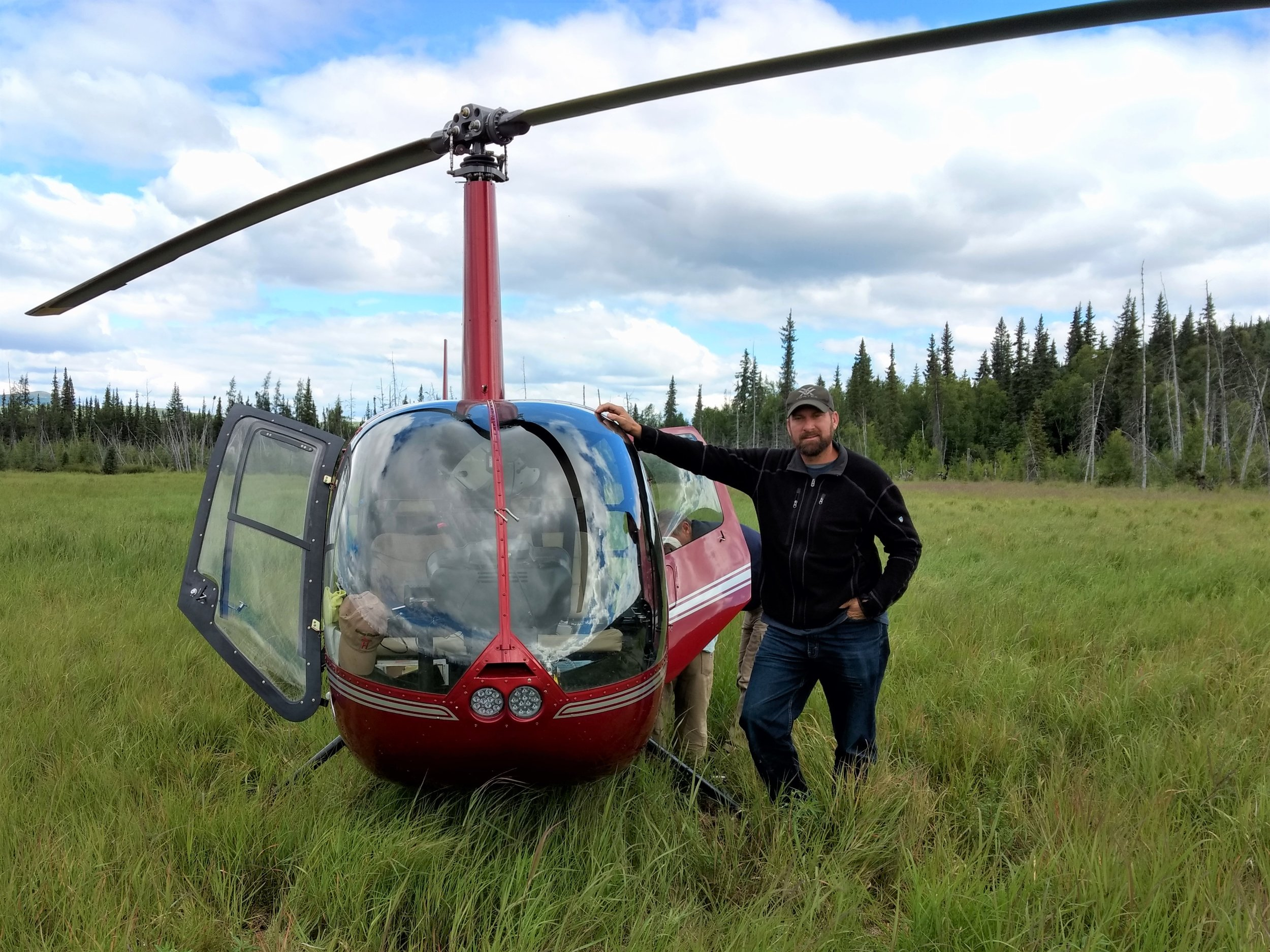 Kevin stark (Saint Mary's University - GeoSpatial Services) and the R44 helicopter landed in a wet meadow.  Photo Credit: Andy Robertson