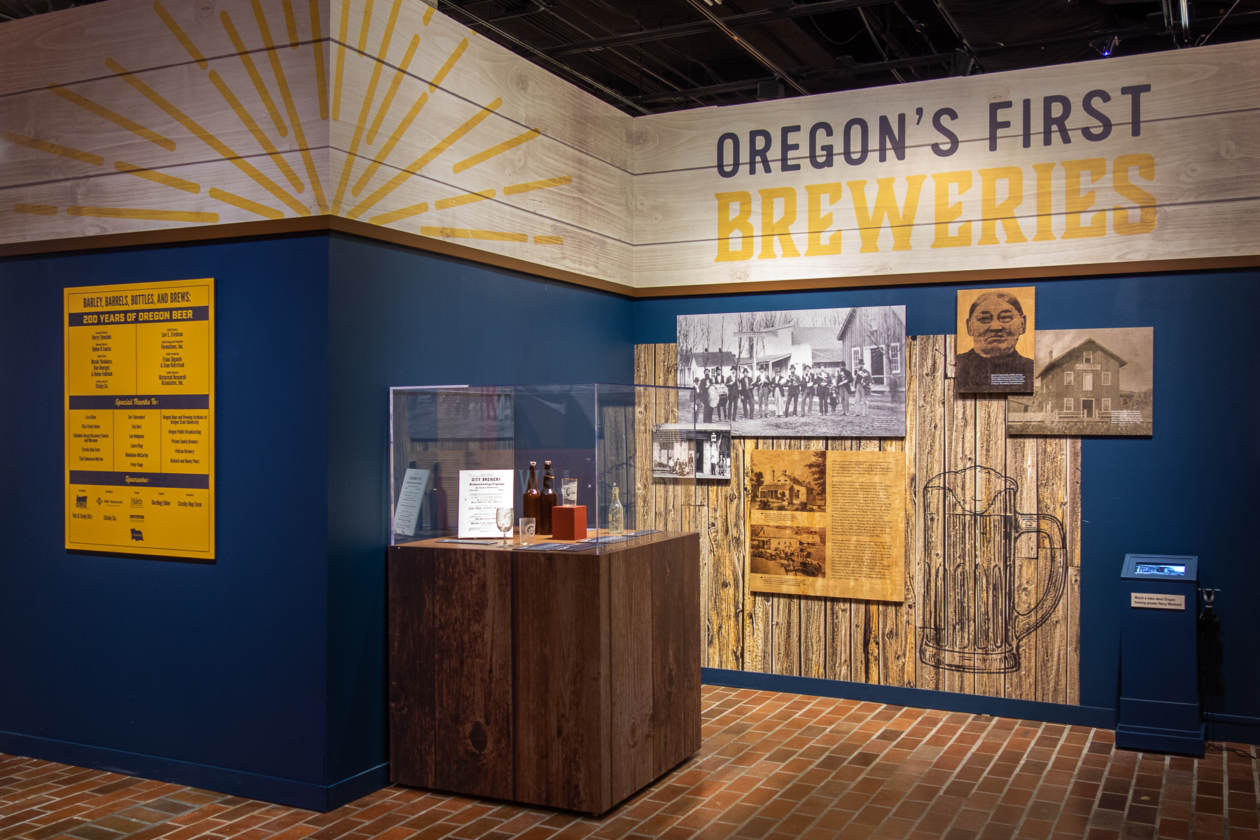 One of the walls that I designed in the opening area of the exhibit showing some of the earliest breweries in Oregon. The heading is a printed vinyl as well as the textured wood/beer stein background. Layered images are directly printed onto black sintra and falcon board.