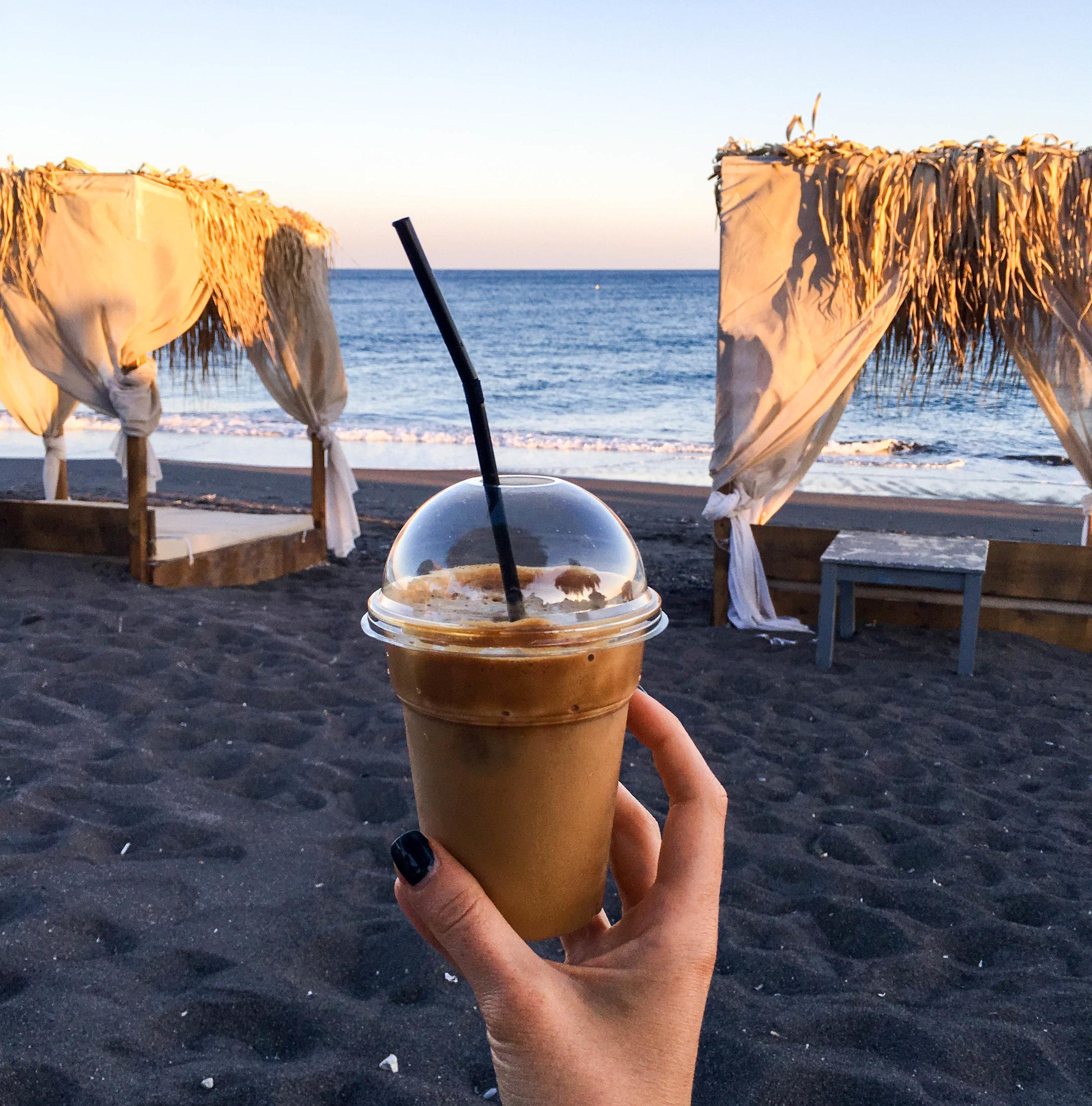 Enjoying a Greek frappe on the black sand beach of Perissa, Santorini, Greece
