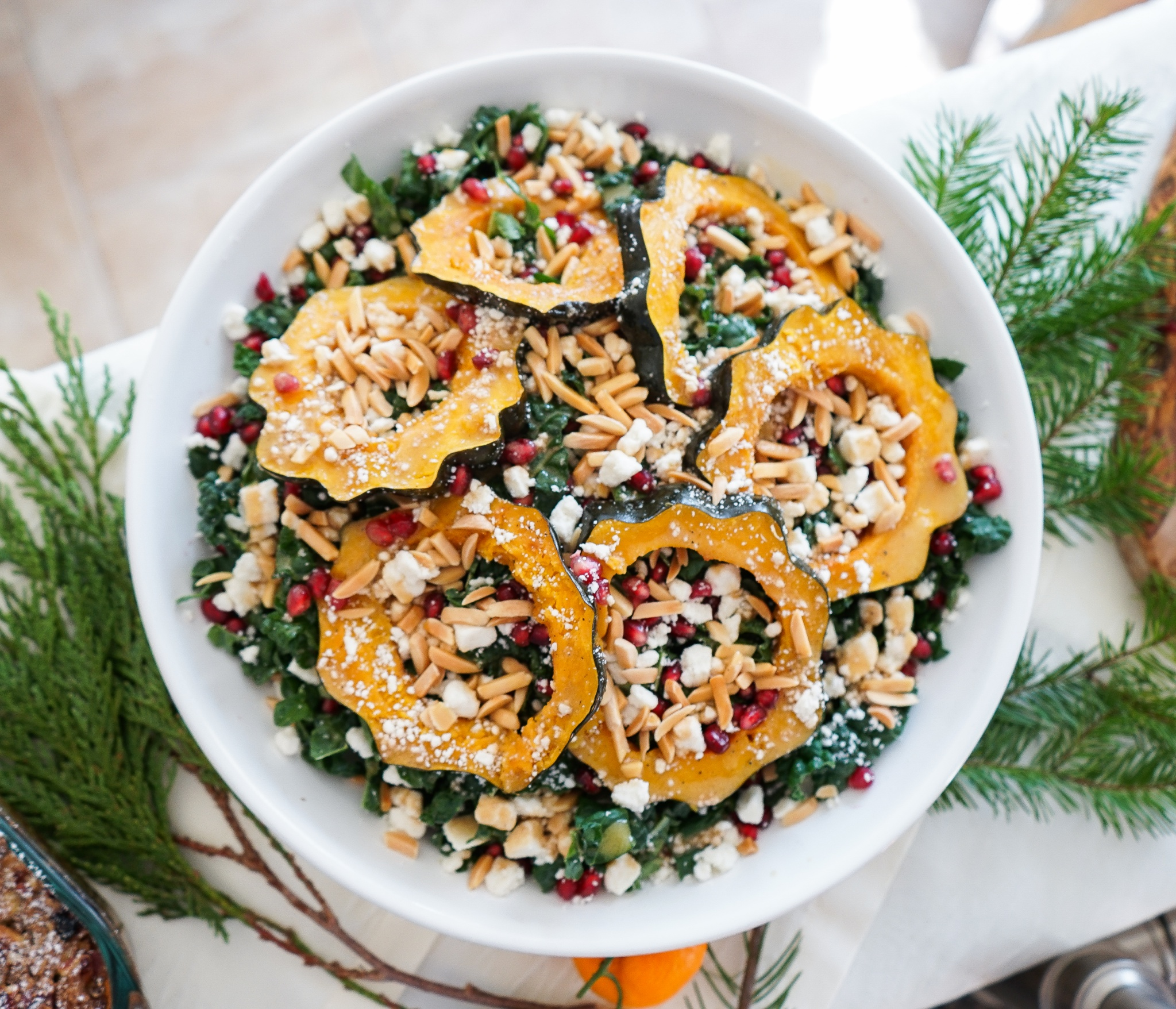 Salad with kale, roasted acorn squash, pomegranate seeds, almonds, and ricotta salata