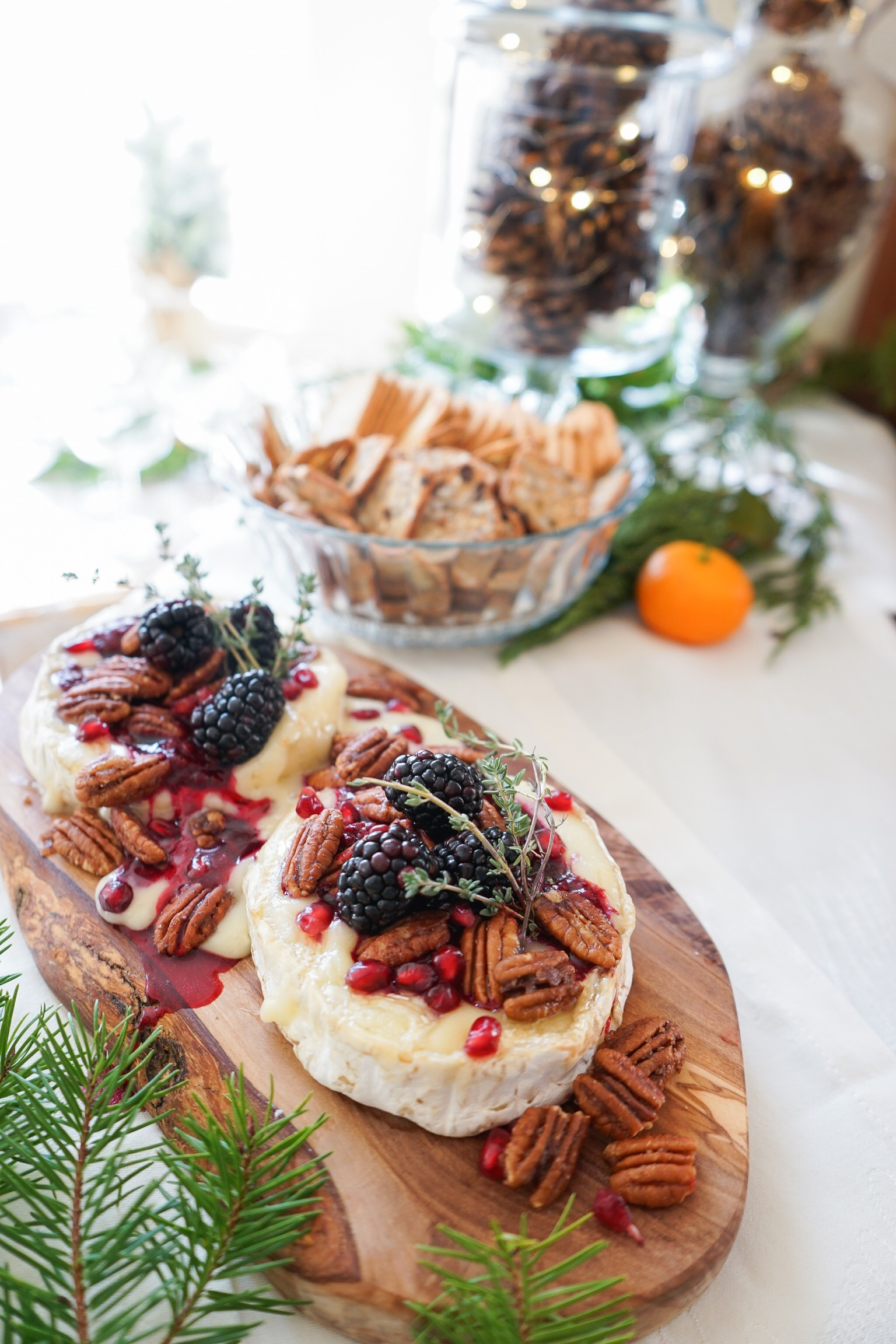 baked brie topped with blackberry compote and toasted pecans and crackers
