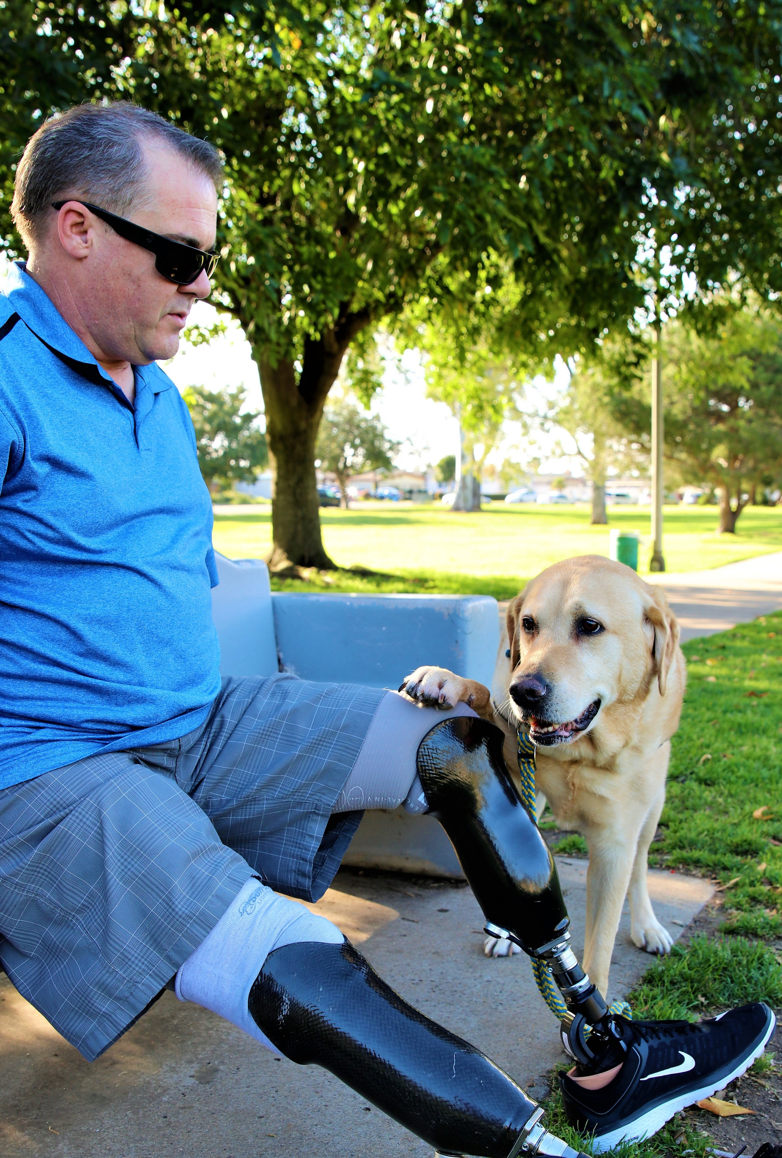 A Caucasian veteran with prosthetic legs looks down at his service dog after the dog puts his paw on the man's knee.