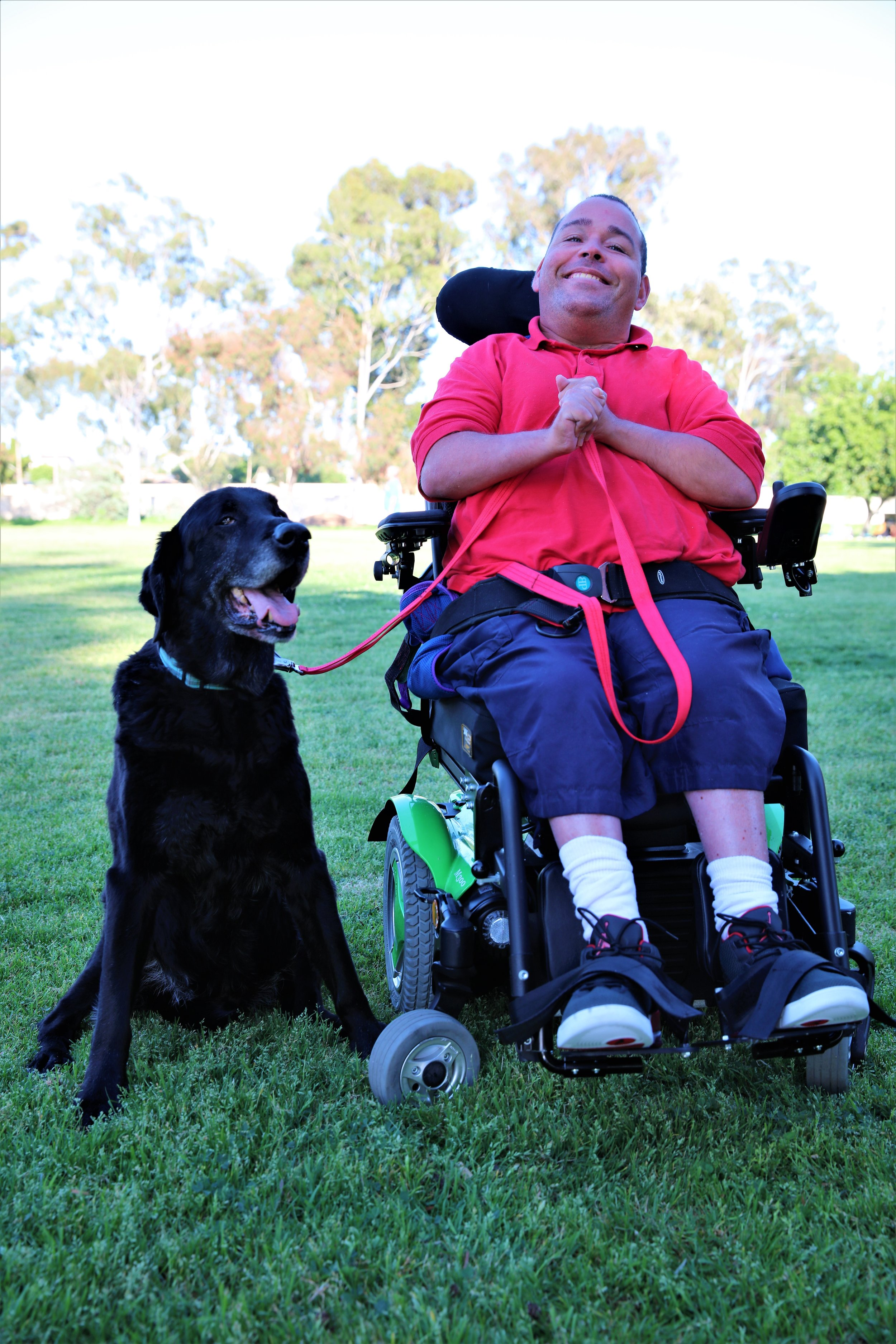 A Caucasian man who is a wheelchair user, poses with his large black service dog.