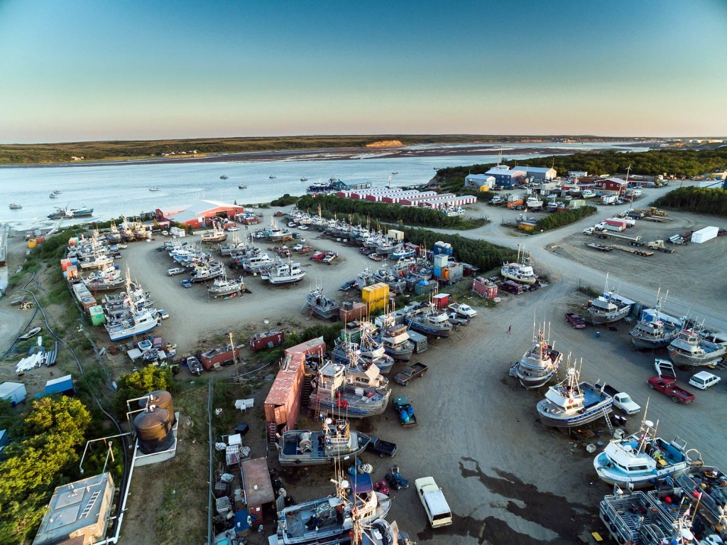 "An aerial view over some of the boatyards that line the Naknek River. Each of the 32′ boats you see represents a small business and a lot of work! The boats anchored in the river are the ones who have already ""splashed."" In a few more days, the boatyards will empty out as salmon enter the Bay and the fleet launches."