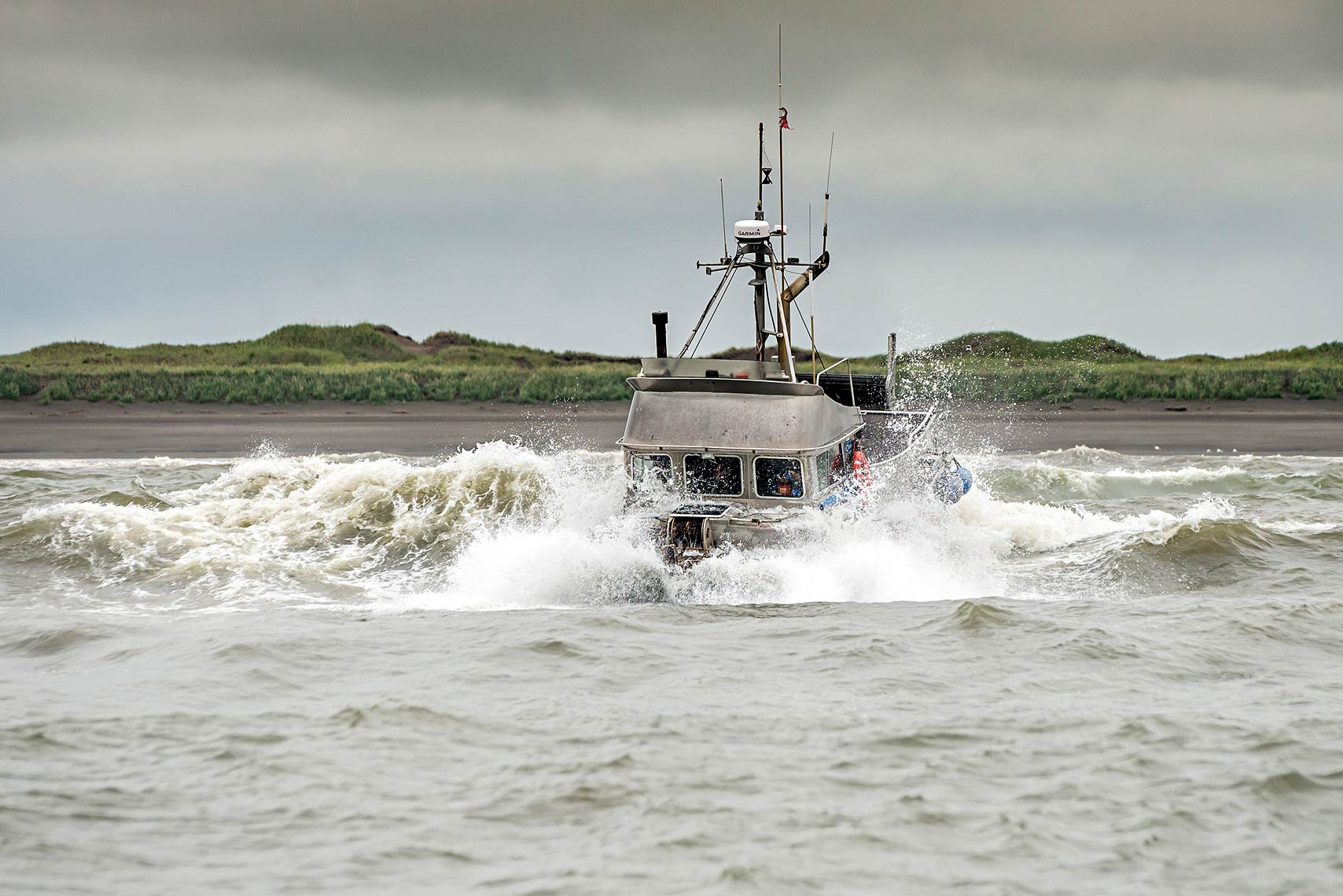 A gillnetter crosses through the breakers to make it out   to the fishing grounds.  Bristol Bay is interweaved with many sandbars and   shoals, and fishermen use the area's many channels to enter and exit   protected waters to access the fishing grounds.