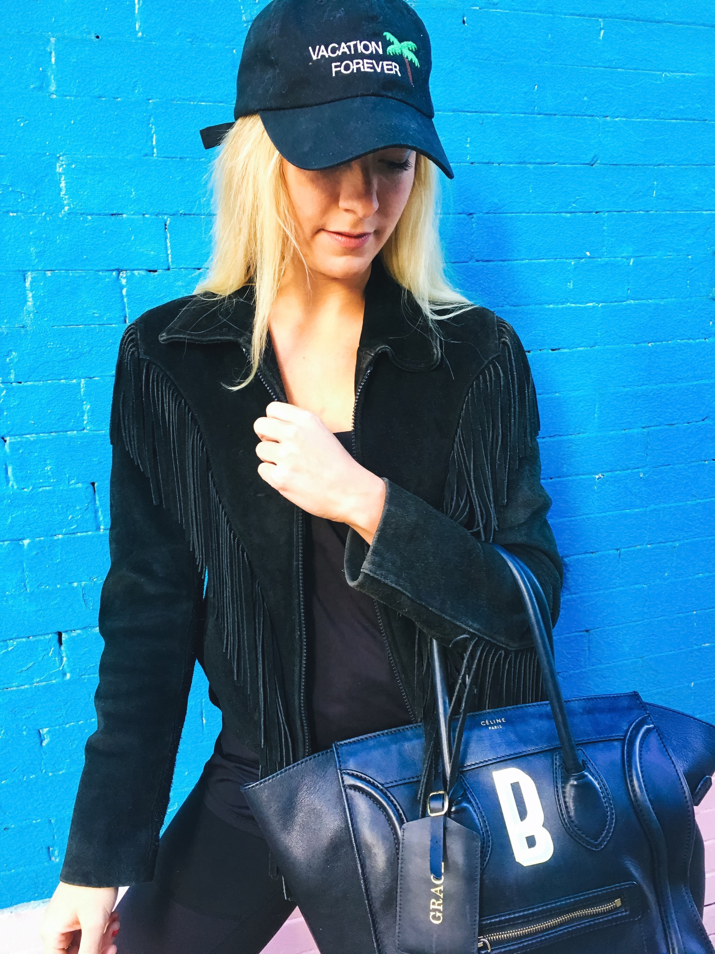 Jacket: The Vintage Twin. Top: The Athleisure Company. Pants: Alo Yoga. Bag: Céline. Luggage Tag: Royce New York. Hat: Red's Outfitters. Patch Sticker: KITSCH.