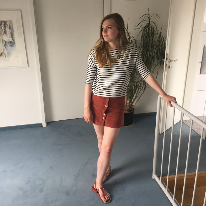 Lily wears a terracotta skirt with gold buttons from Miss Selfridge with matching sandals and a striped jumper. Her gold vintage necklace coordinates with the gold on the skirt and the shoes.