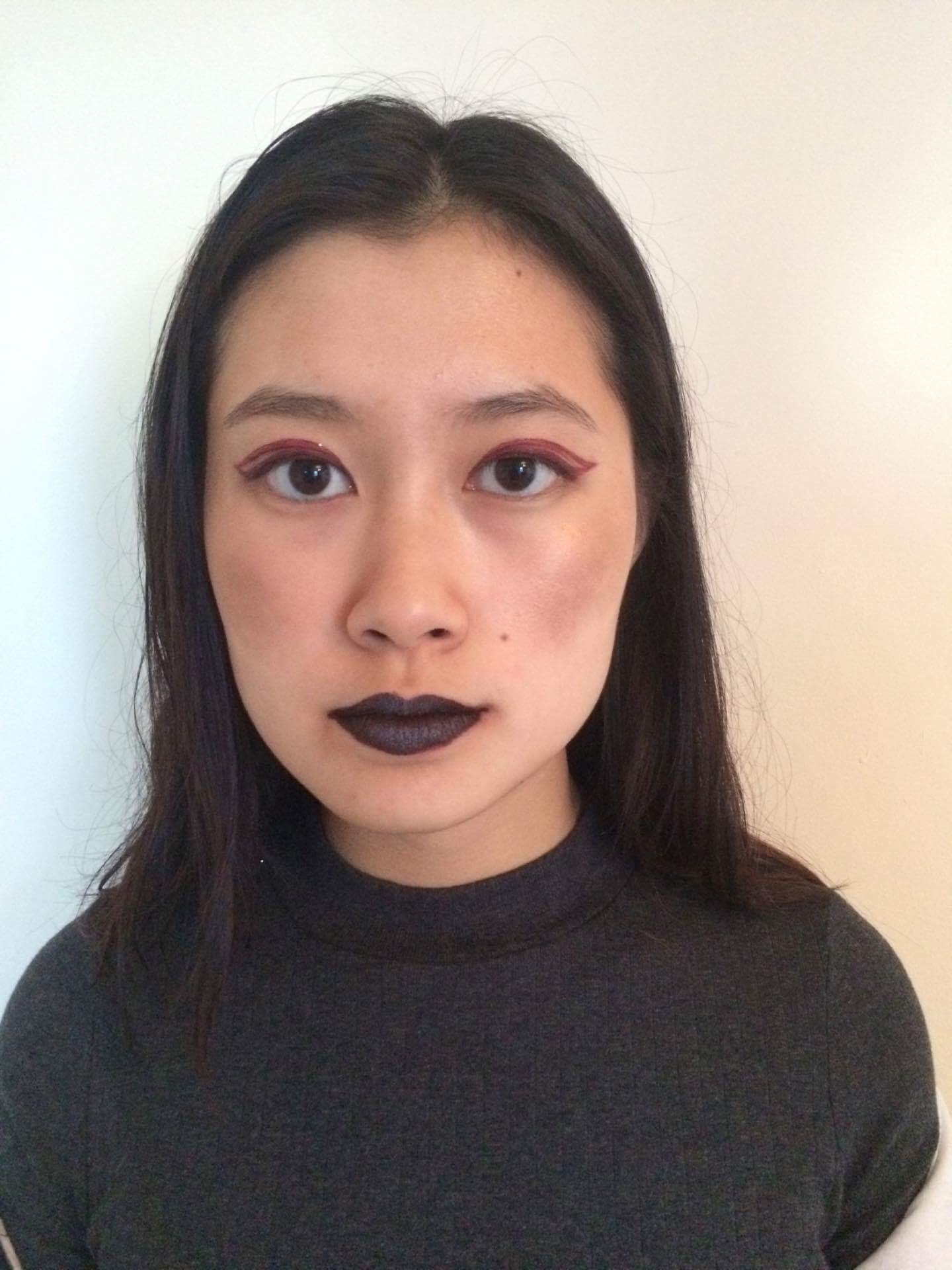 Nicole Ip wears Milk Makeup's Dip Out lip color on her eyes, glitter eyeshadow on her cheeks, and Kat Von D liquid lipstick with the Kat Von D Alchemist shadow ultra-violet on her lips.
