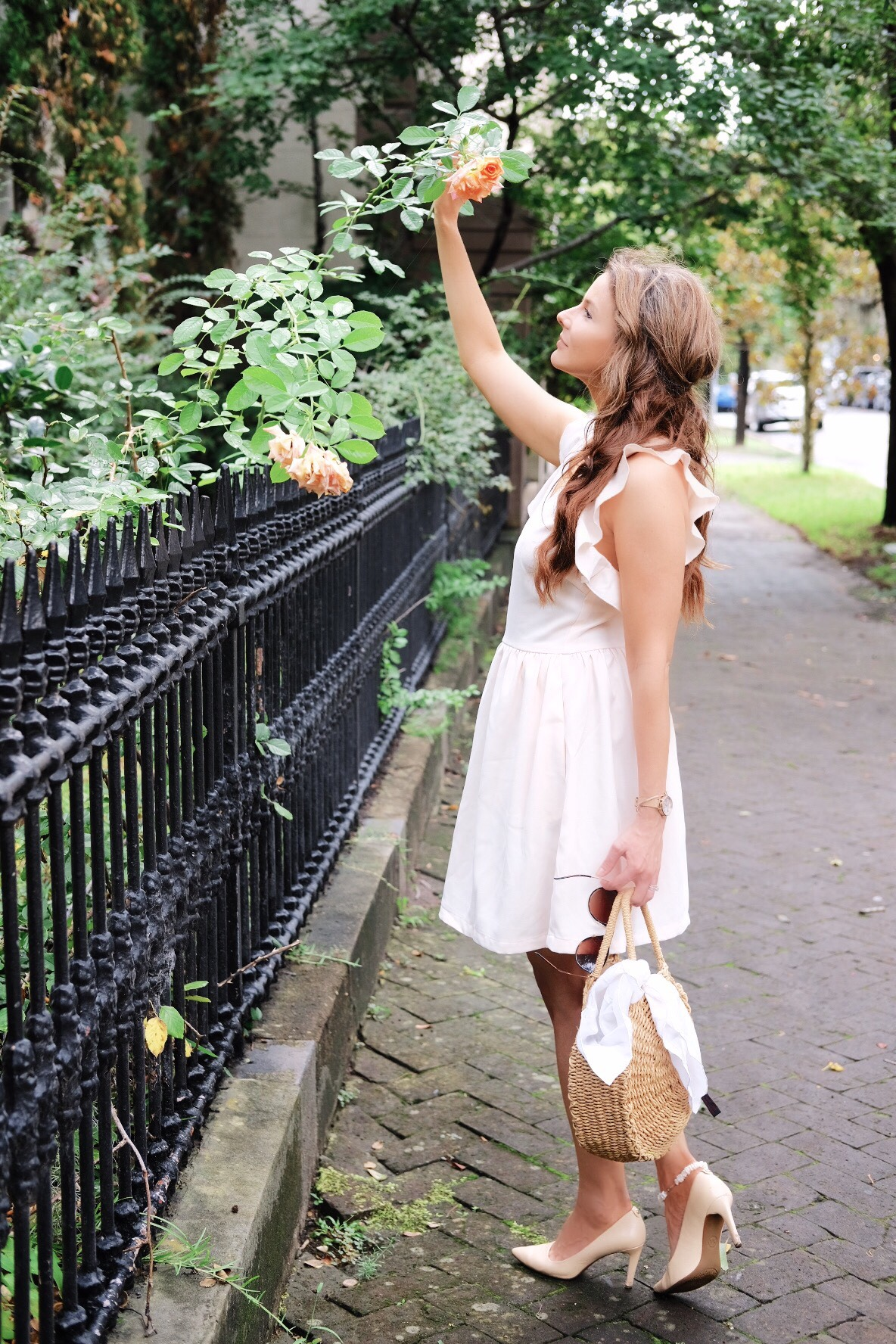 Brenna Lauren Michaels standing on cobbled street by rosebush, wearing blush pink frilly dress.