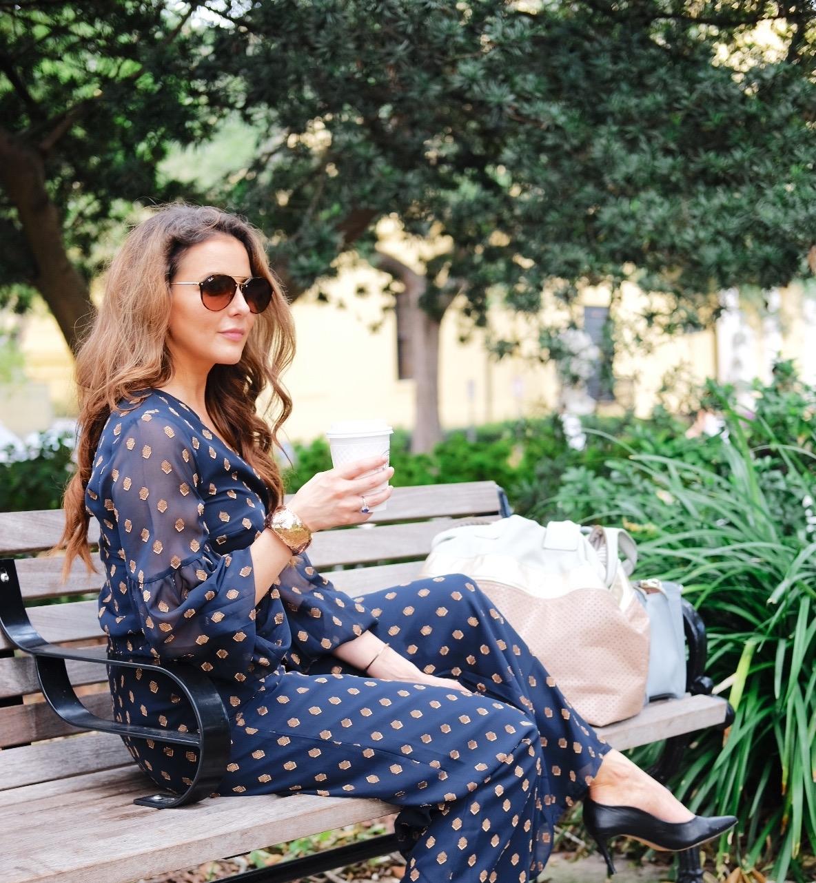 Brenna Lauren having coffee on bench in Navy Blue jumper
