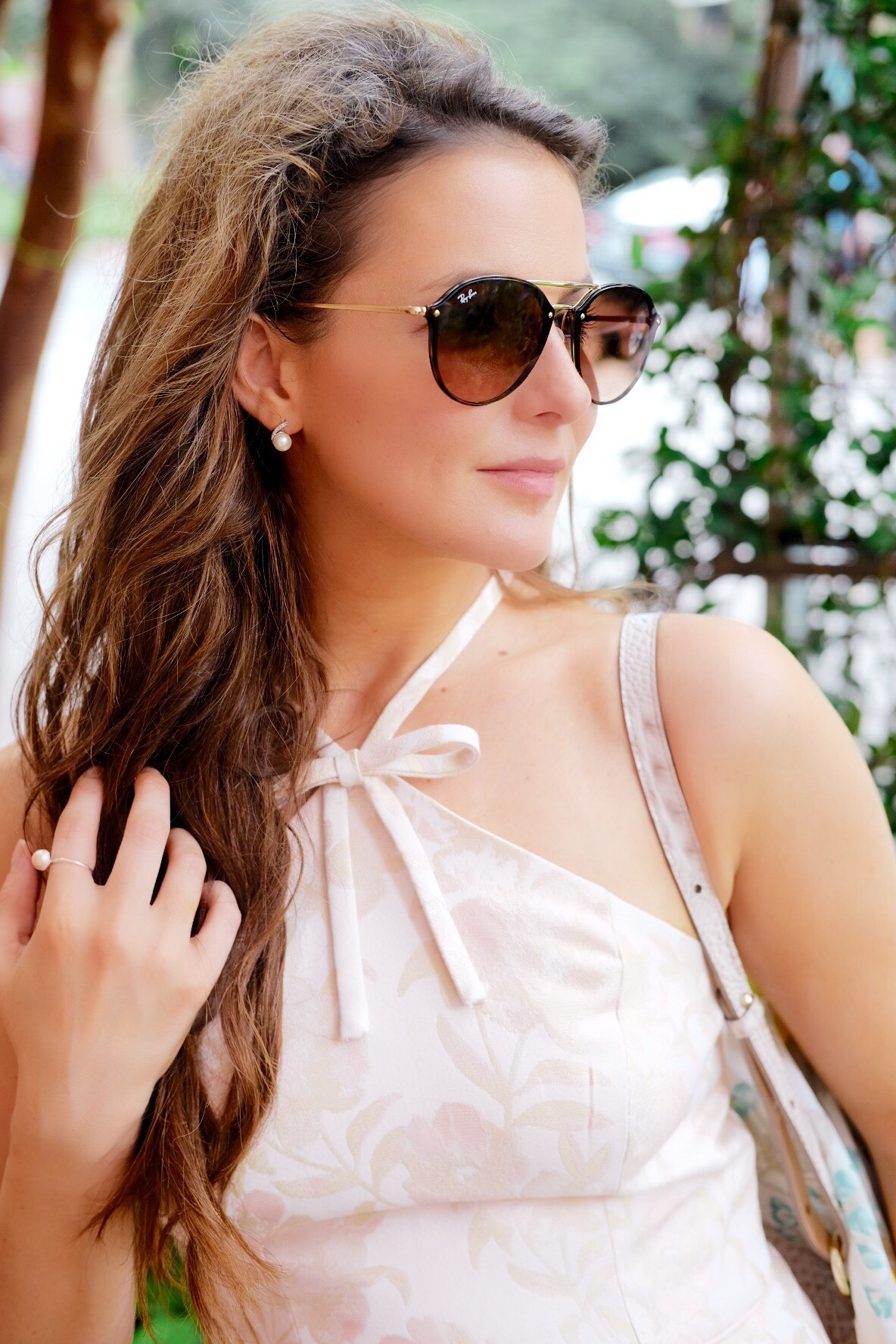 Brenna Lauren in blush pink gal meets glam dress with bow, pearl earrings, and ray bans