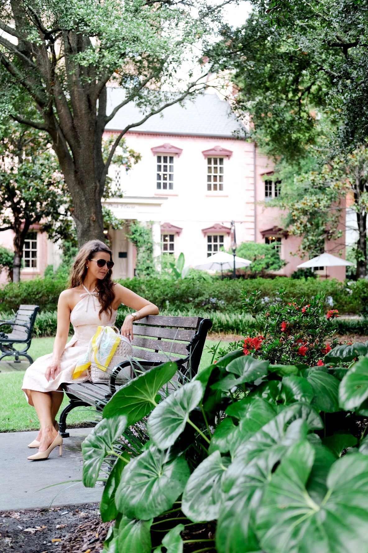 Brenna Lauren on bench outside of Olde Pink House in Gal Meets Glam blush pink dress