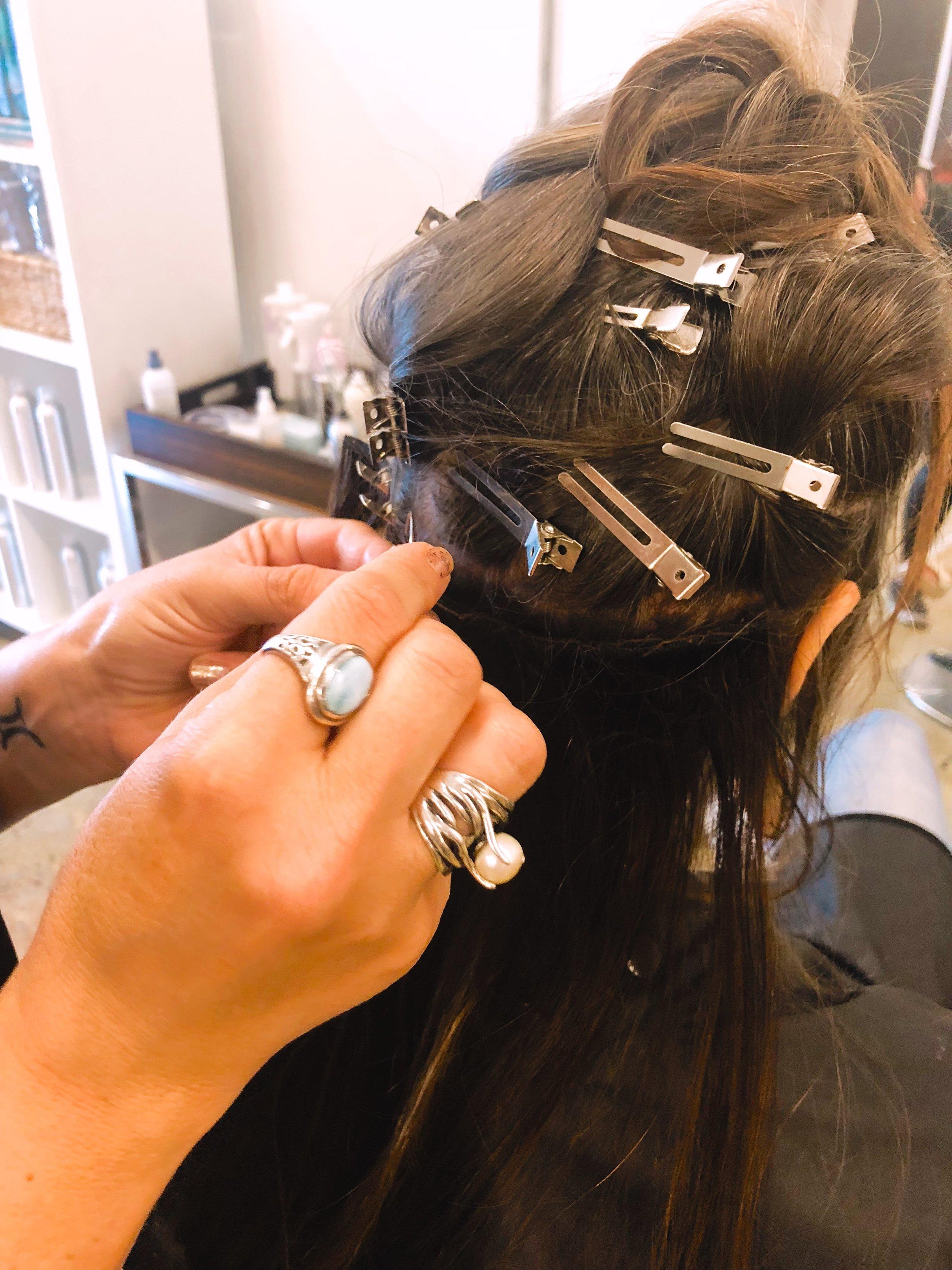 Pepper weaving hair extensions into Brenna's hair