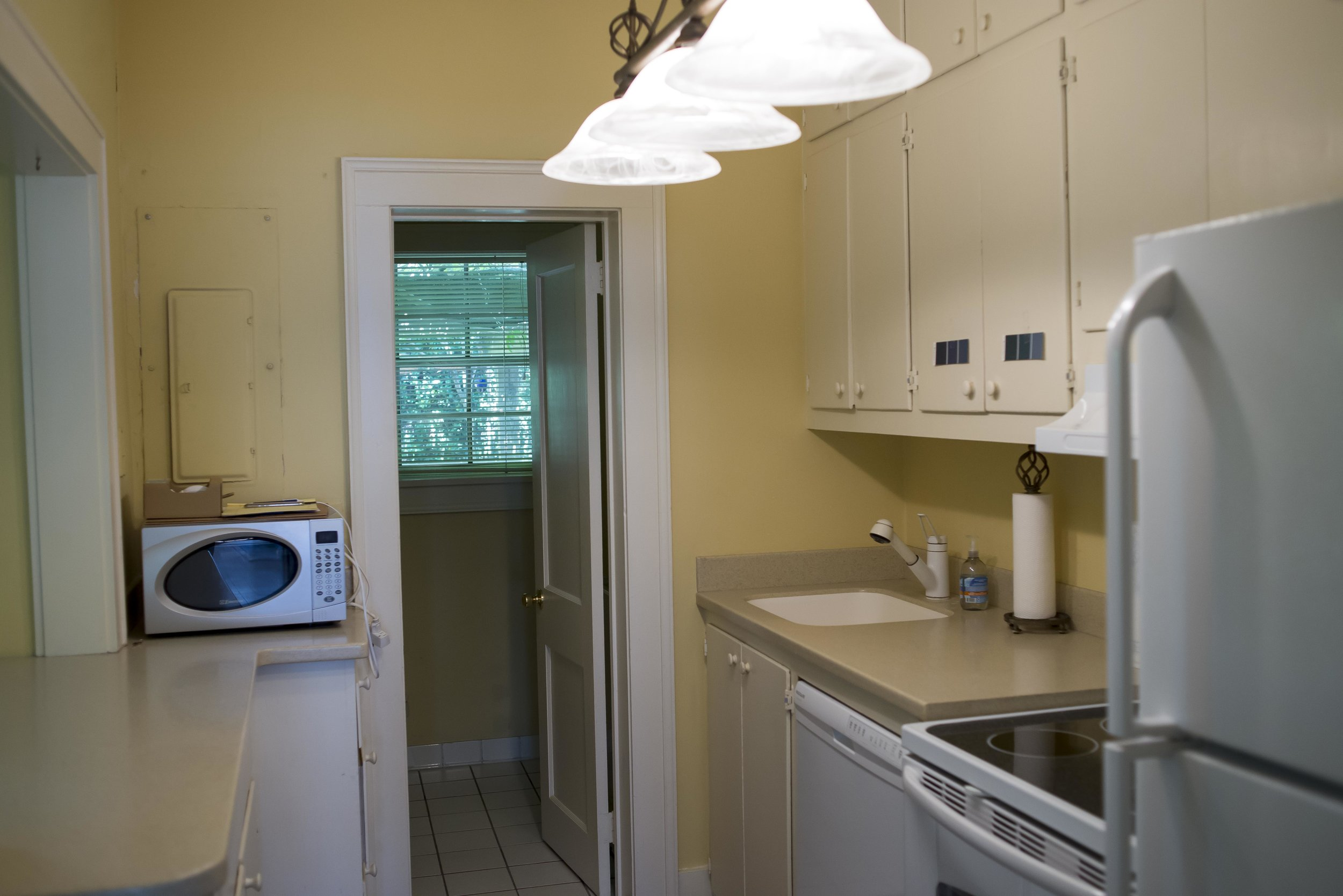 The kitchen, with adjacent powder room . . . if you tried really hard you could stick your toe out and touch the kitchen sink cabinet while sitting on the toilet. Super classy.