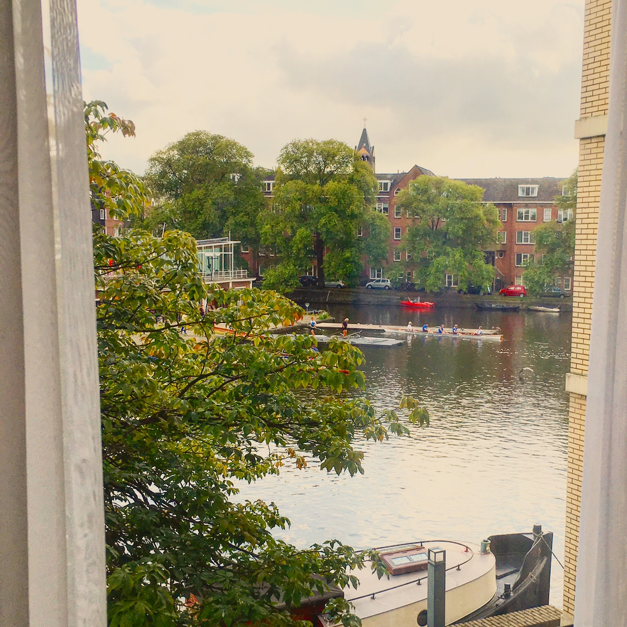 "In the morning, people docking and renting boats at the Roei- en Zeilvereniging ""De Amstel"" boating club outside of my window."