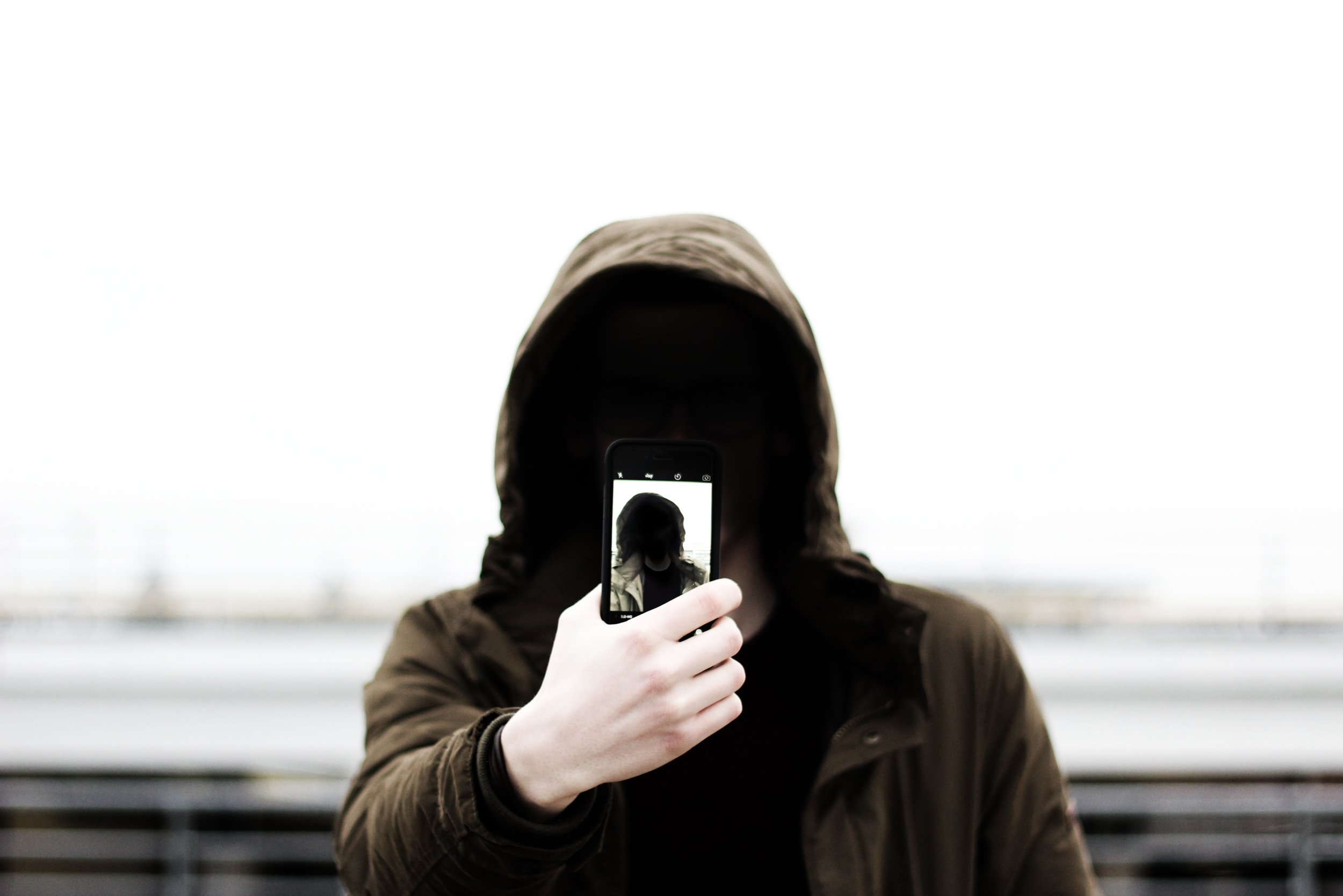 www.mgmstraining.ie/hooded man holding phone in front of his face