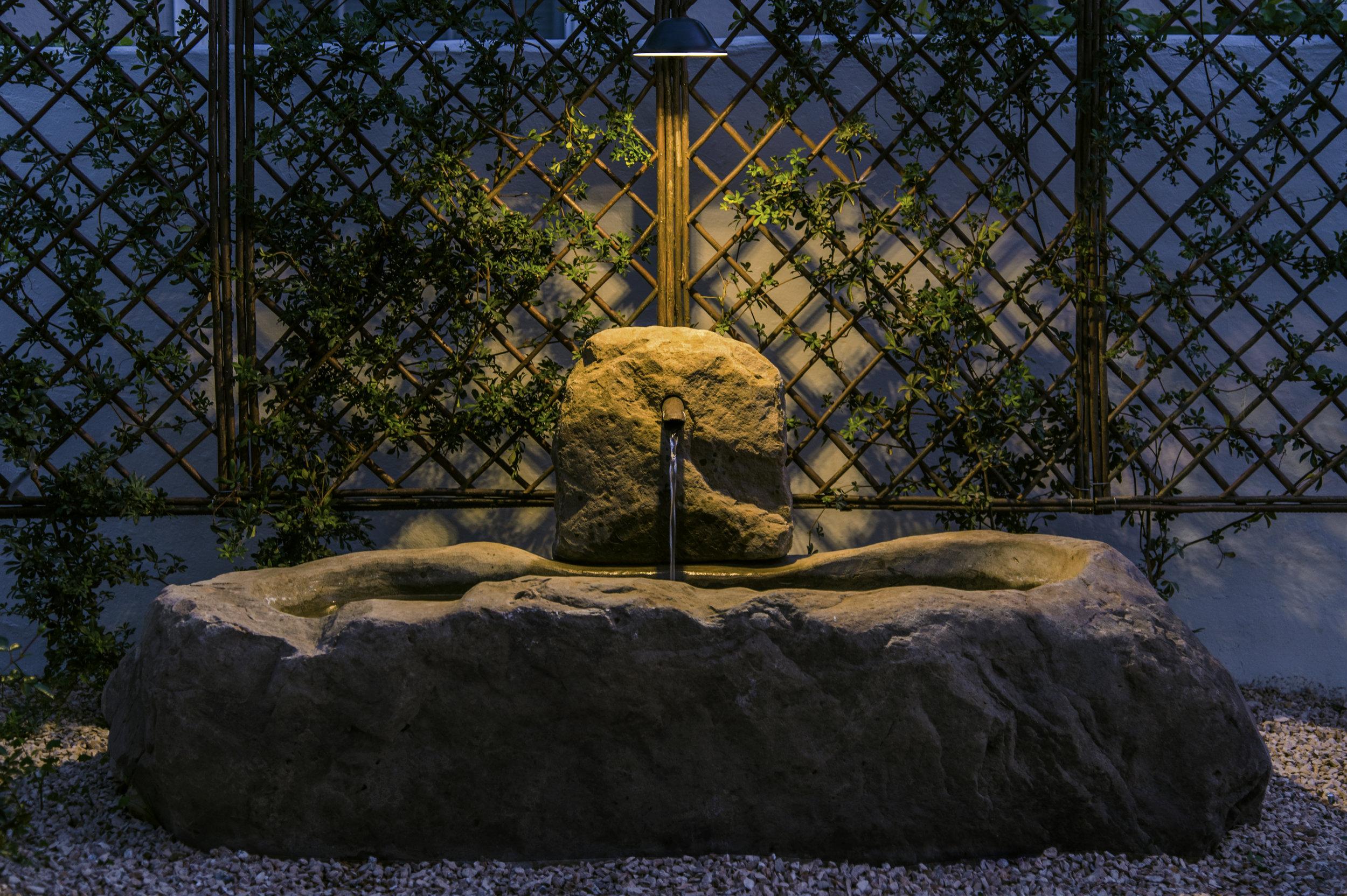 drought tolerant landscape with stone fountain