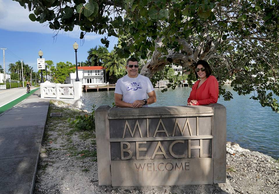 Residents of Biscayne Island, Diana Fontani and Mario Reyes, stand by the Welcome to Miami Beach sign that marks the boundary between Miami and Miami Beach.