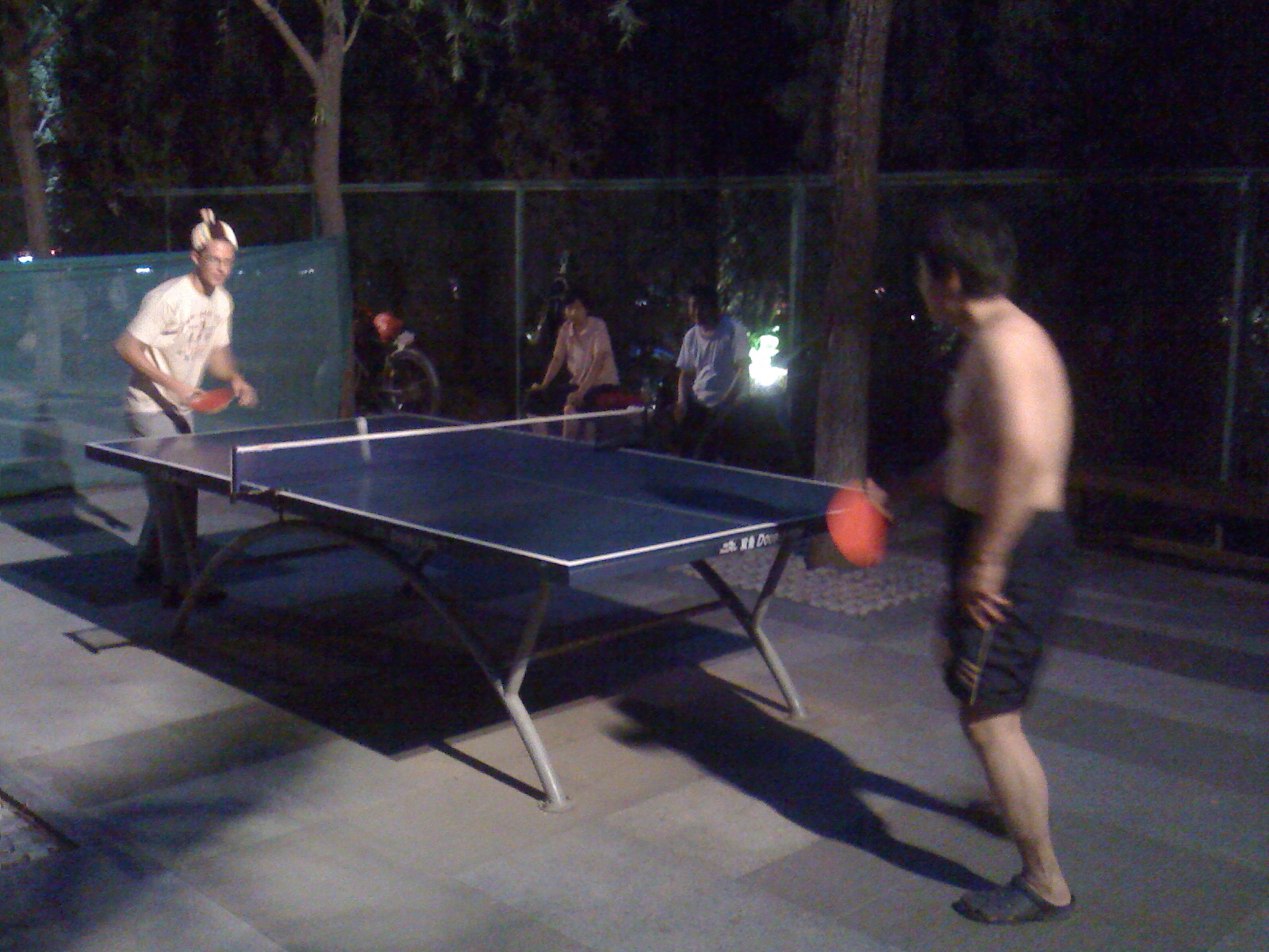 Marks takes on nitetime outdoor Pong with random Chinese guy.