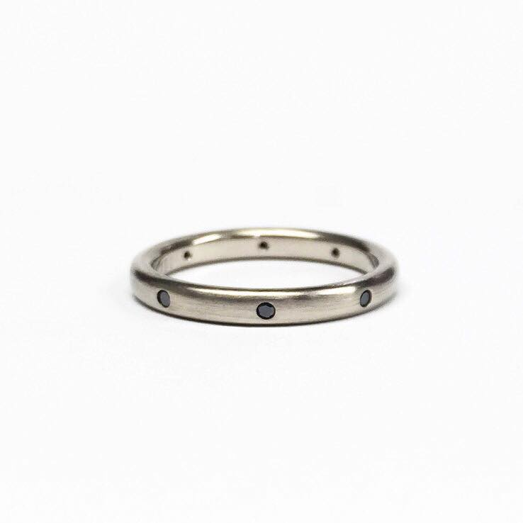 "Handmade wedding band in ""raw"" white gold and set with black diamonds."