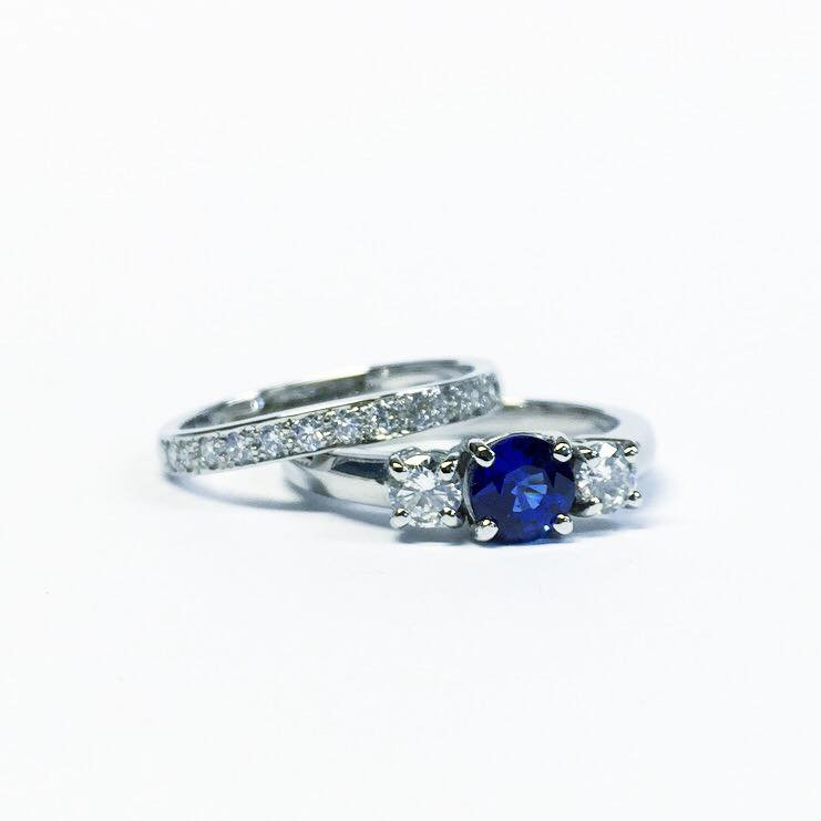 A custom made engagement ring in platinum set with a stunning Ceylon sapphire and diamonds and a diamond set wedding band.