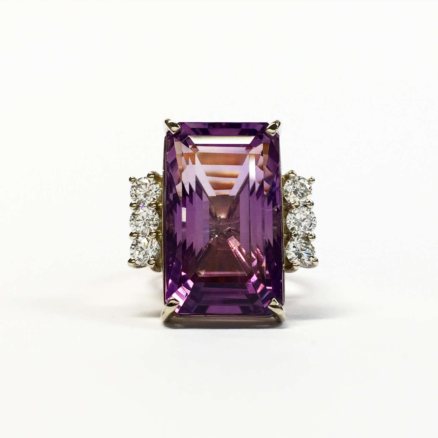 Handmade cocktail ring in yellow and white gold set with a large emerald-cut amethyst and diamonds.