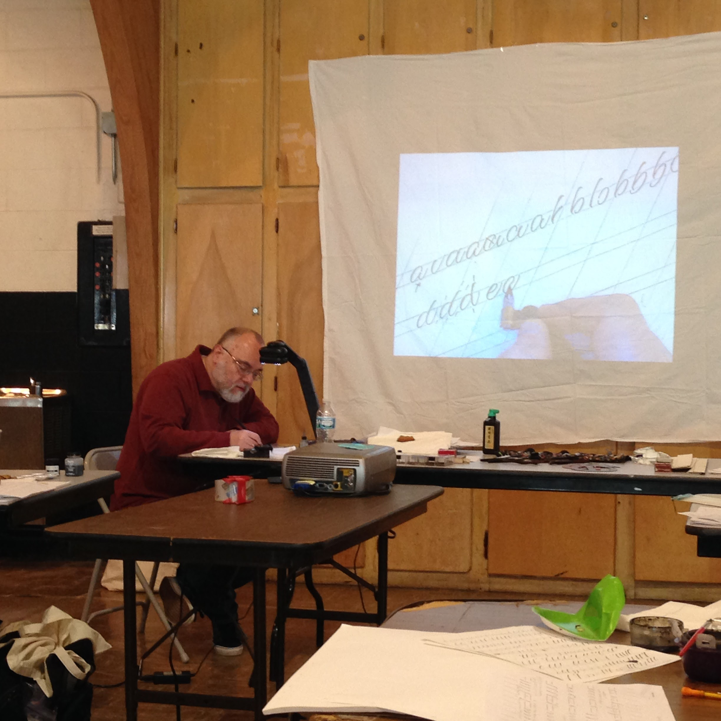 Mike Kecseg demonstrating lettering techniques with a projector