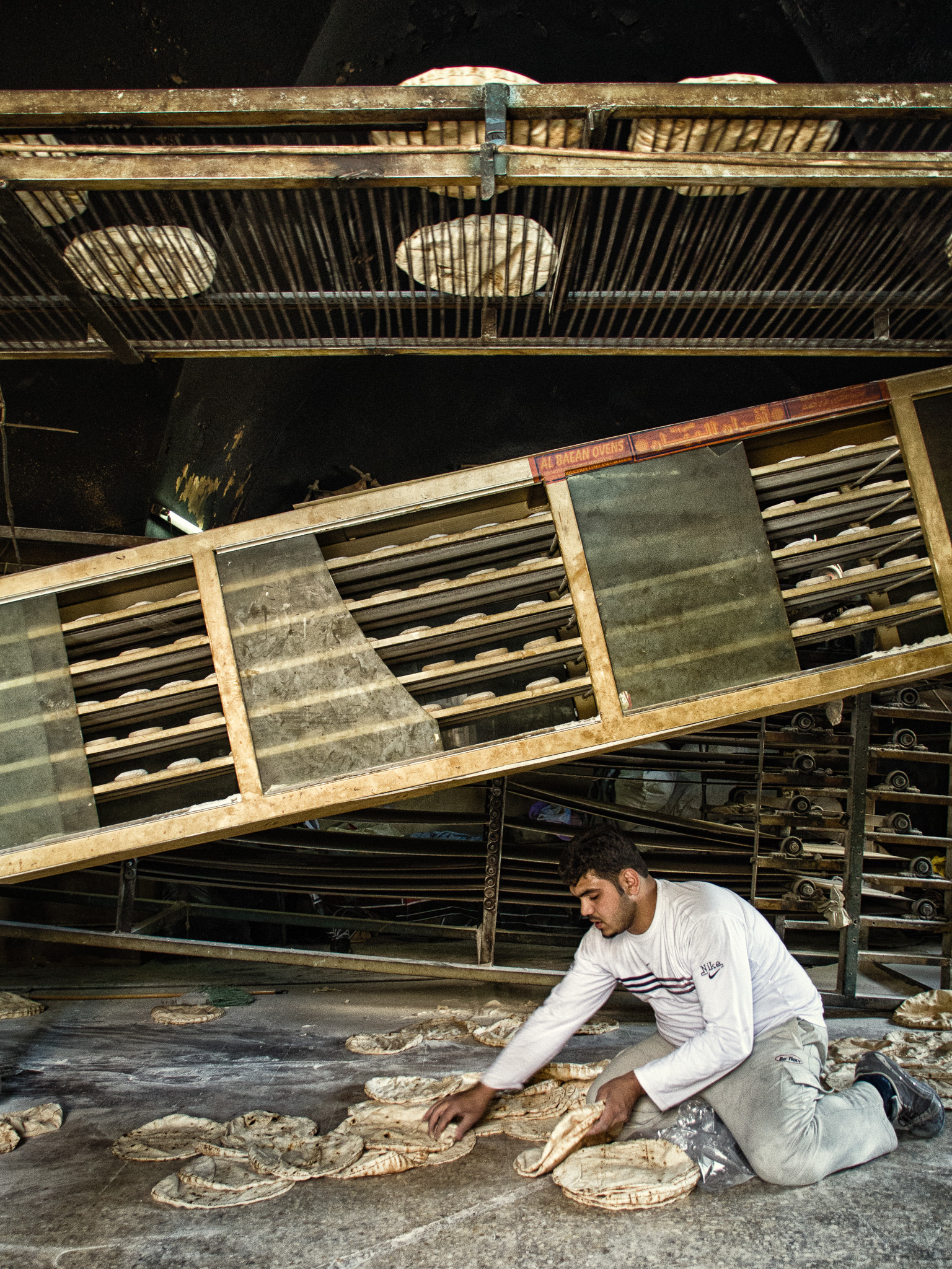 An old industrialized bakery has conveyor belts crisscrossing a rather large space, before dumping the breads onto the floor for sorting and packing by hand (Aleppo).