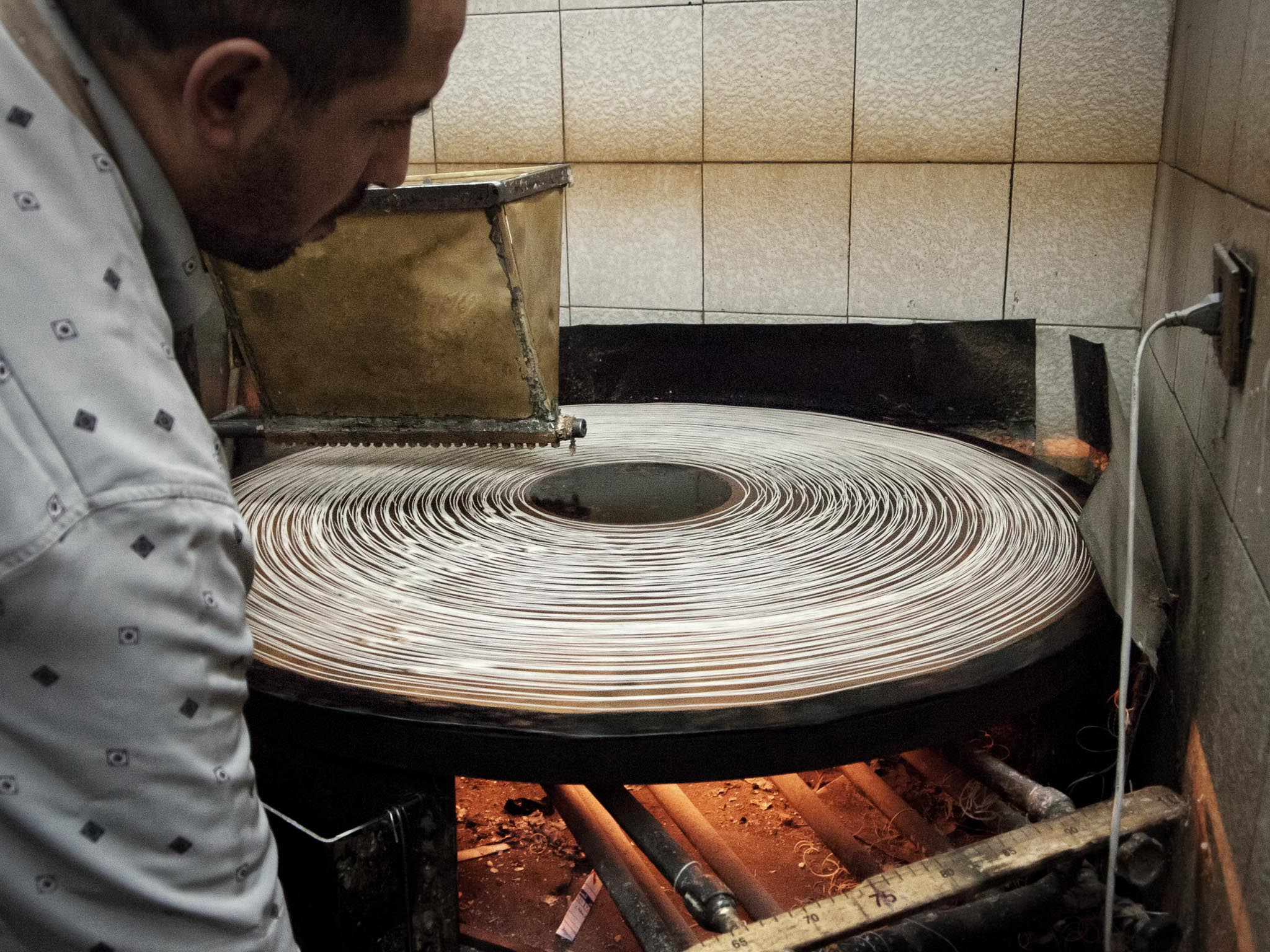 Ever wondered how the stringy bits in baklava is made? A runny dough is pored into the triangular container, which has a series of small holes at the bottom. The dough drops onto a rotating, hot steel plate. Once finished, the baker gathers the baked strings to place onto trays where the rest of the various ingredients are layered (Aleppo).