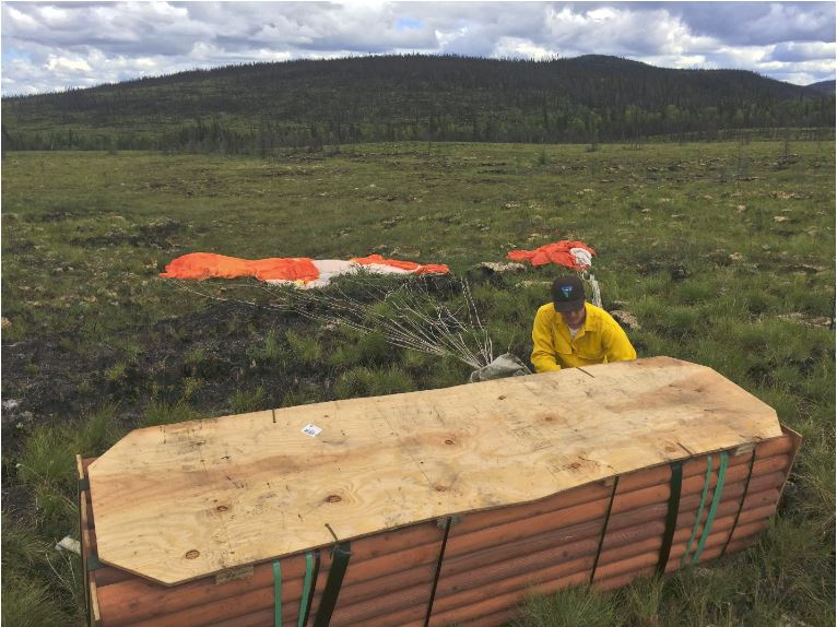 A BLM crew member collecting a parachute attached to a bundle of wooden tripods brought out on the trail in a paracargo delivery.