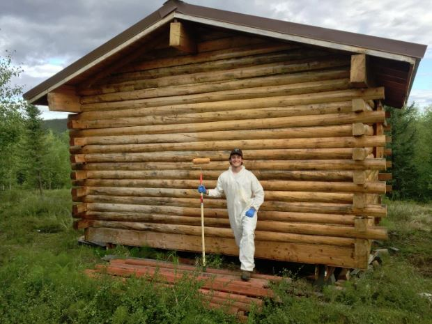 A BLM trail maintenance crew member posing in front of a public shelter cabin with recently oiled logs.