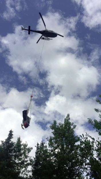 Helicopter helping to remove an abandoned snowmobile from the Iditarod National Historic Trail.